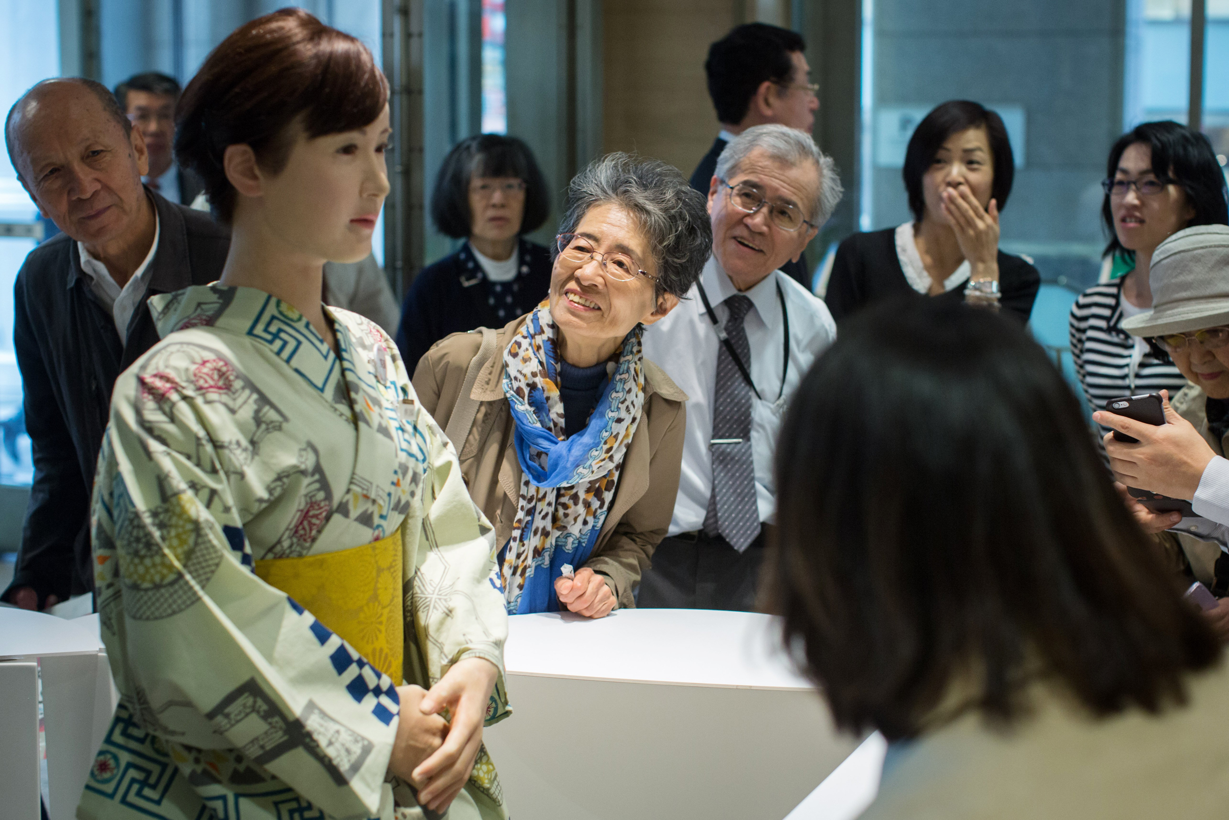 Shoppers view and take photographs of humanoid robot aiko chihira