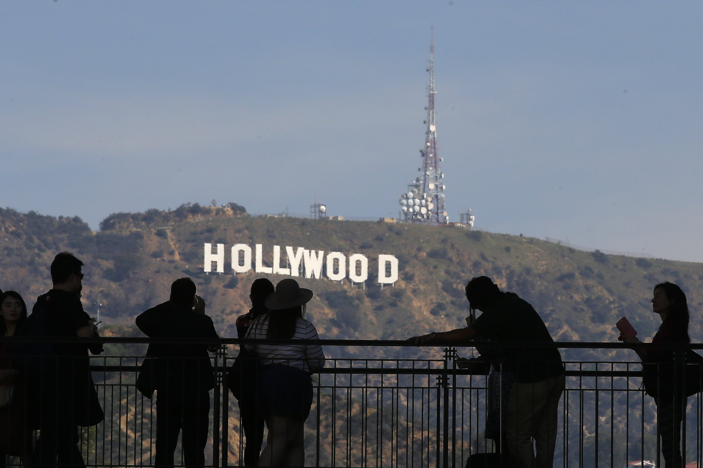 Image: People look on and photograph the famed Hollywood sign as preparations continue for the 88th Academy Awards in Hollywood, Los Angeles