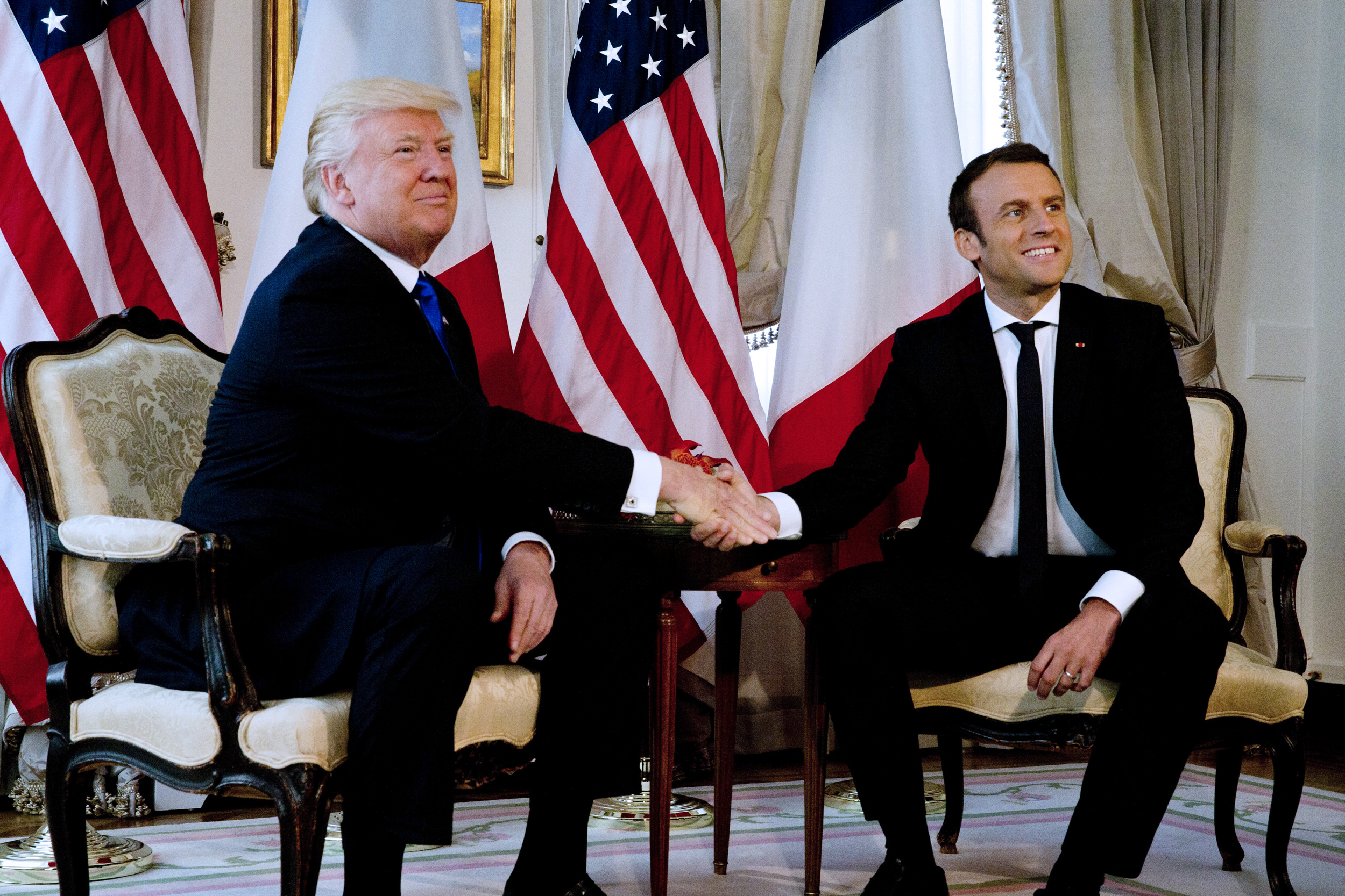 Image: President Donald Trump shakes hands with French President Emmanuel Macron in Brussels