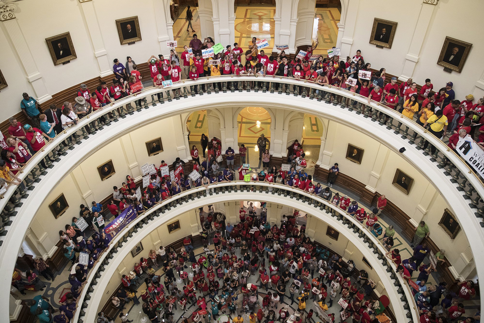 Image: Hundreds of protesters line the balconies of the state Capitol rotunda in Austin