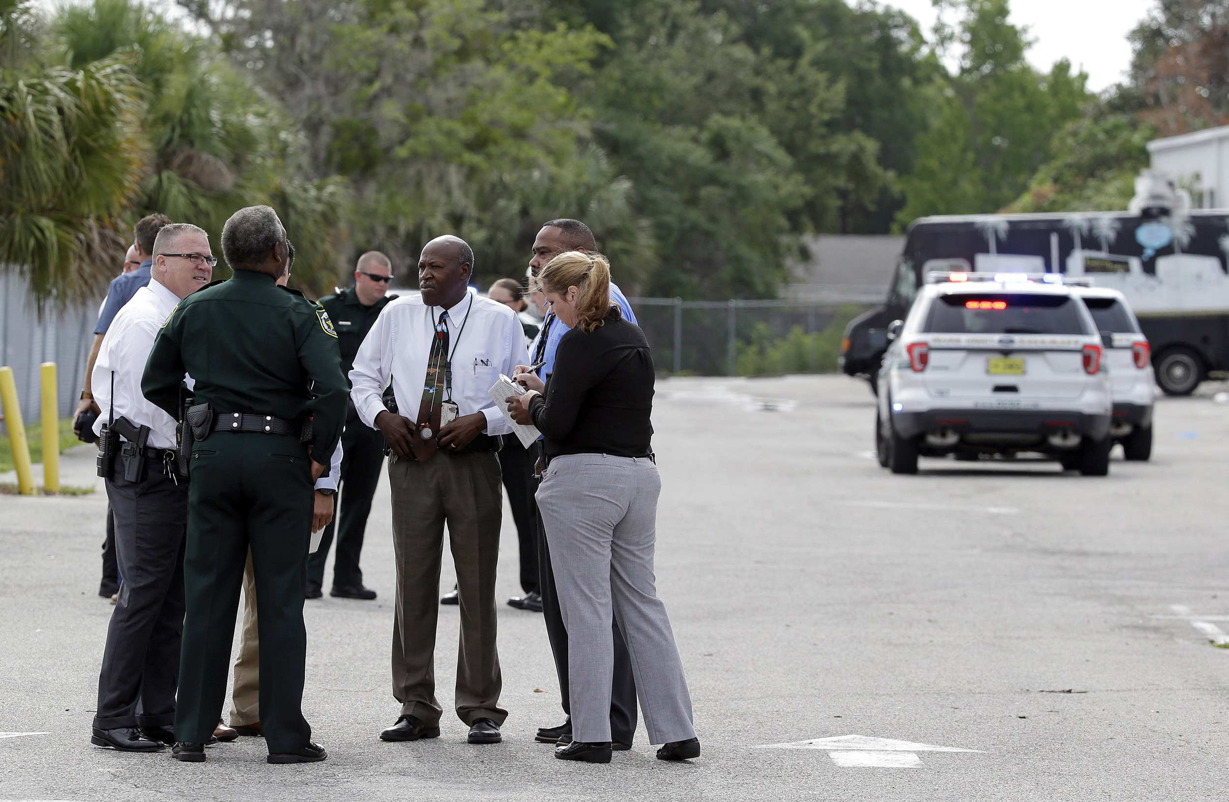 """Image: Authorities confer, June 5, 2017, near Orlando, Florida. Law enforcement authorities said there were """"multiple fatalities"""" following a Monday morning shooting in an industrial area near Orlando."""