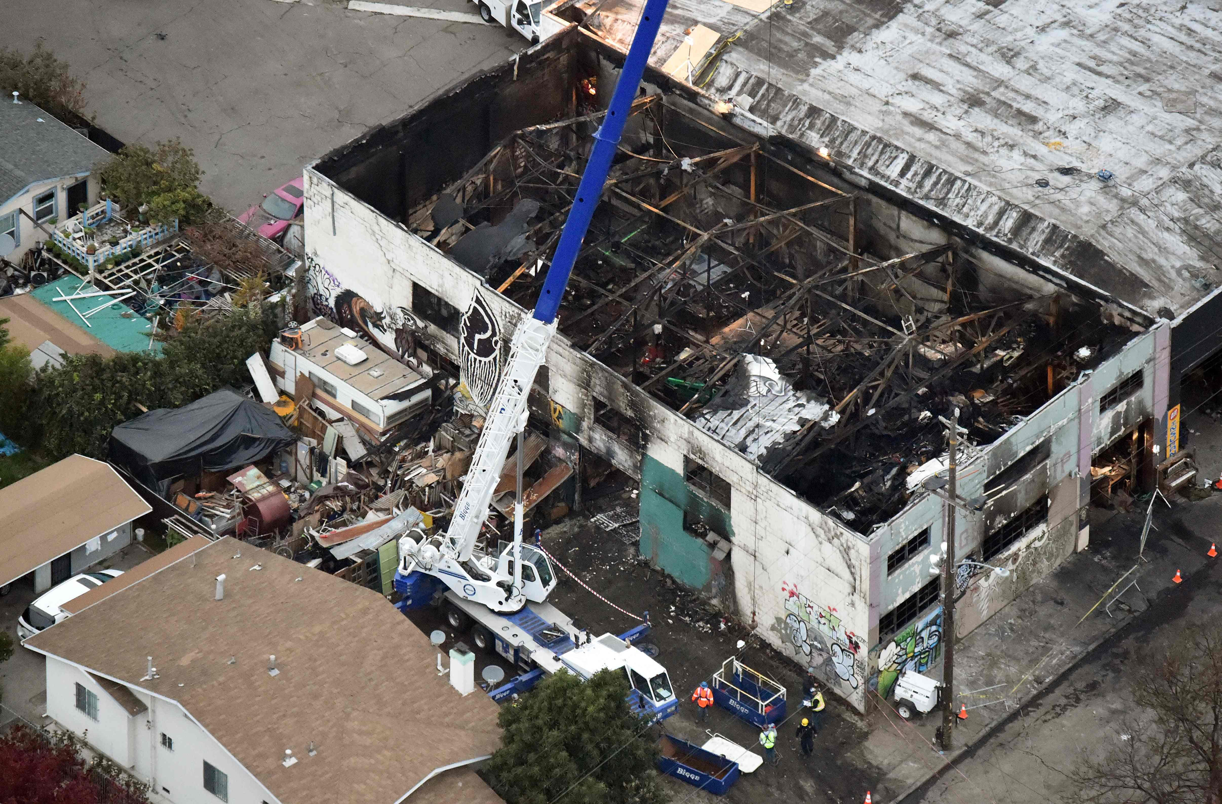 Image: A crane is used to lift wreckage in a fire-ravaged warehouse in Oakland