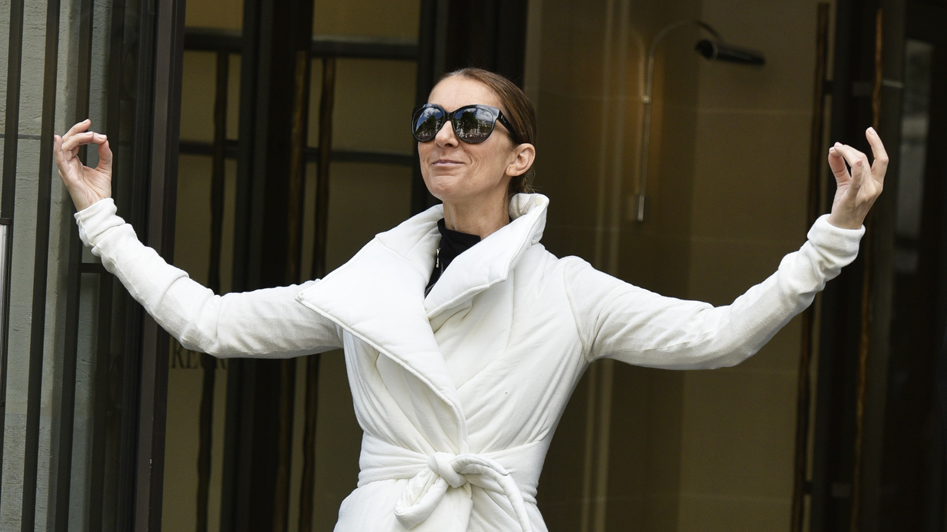 Celiné Dion strikes yoga poses for photographers outside Paris hotel