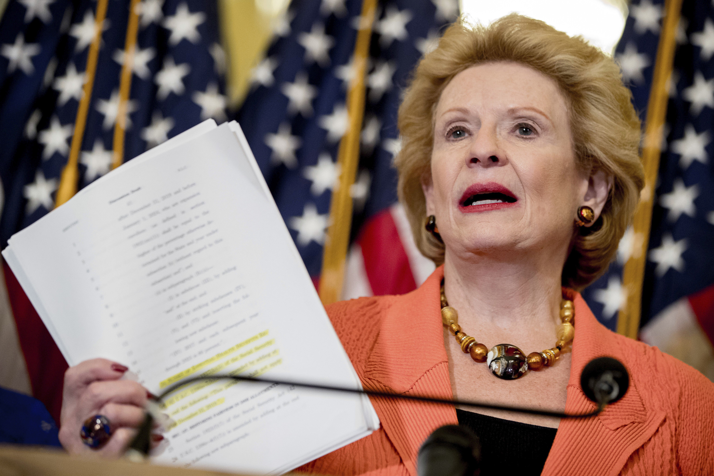 Image: Debbie Stabenow holds up a copy of the proposed Senate Republican health bill