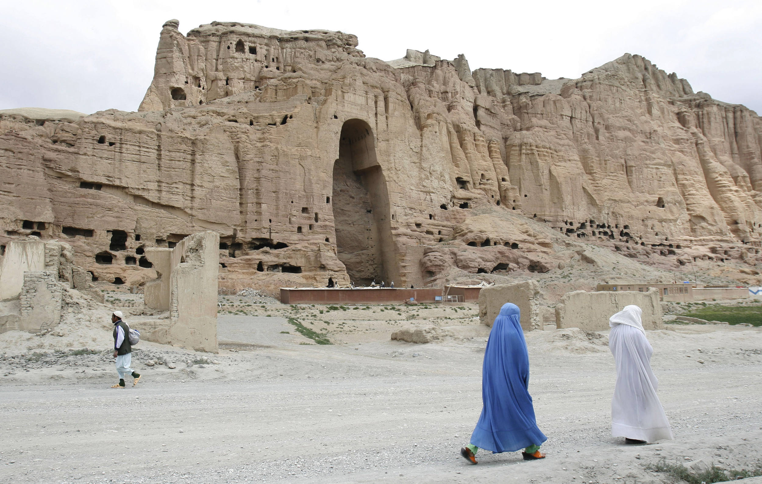 Image: Women walk past cliffs in Bamiyan, Afghanistan