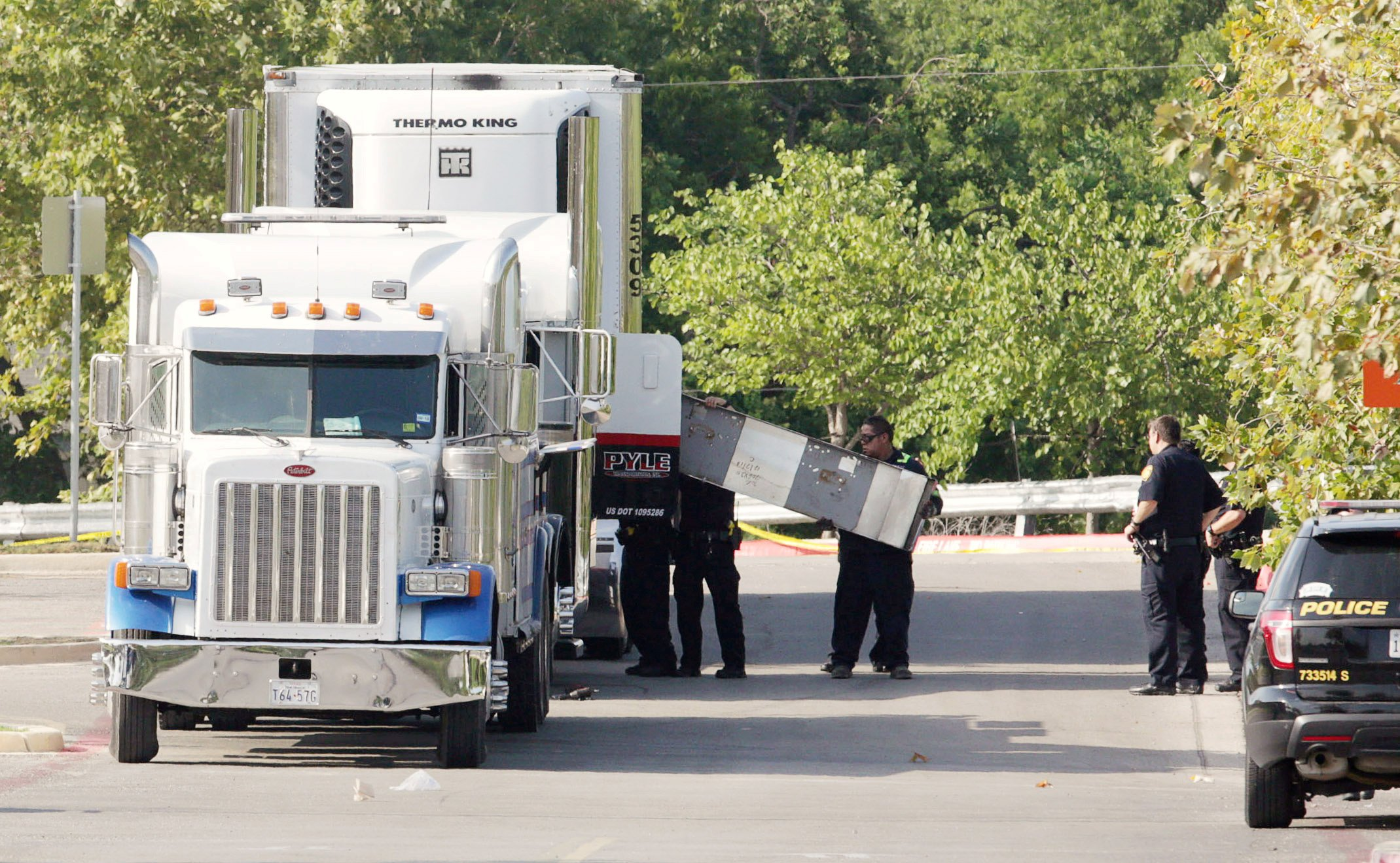 Image: Police work on a crime scene after eight people were found dead inside a sweltering 18-wheeler in San Antonio.