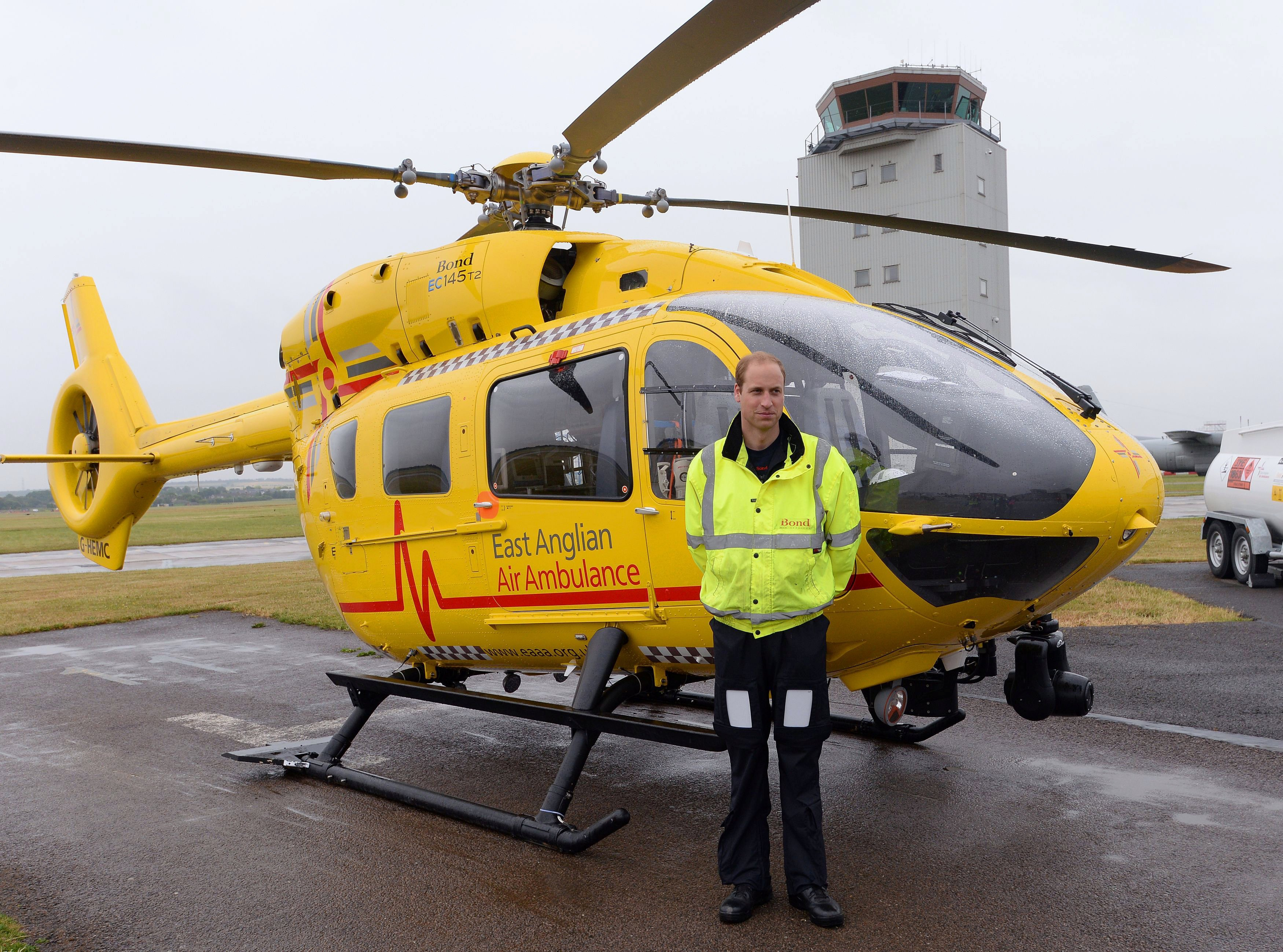 Britain's Prince William poses by his helicopter as he begins his new job as a co-pilot with the East Anglian Air Ambulance at Cambridge Airport