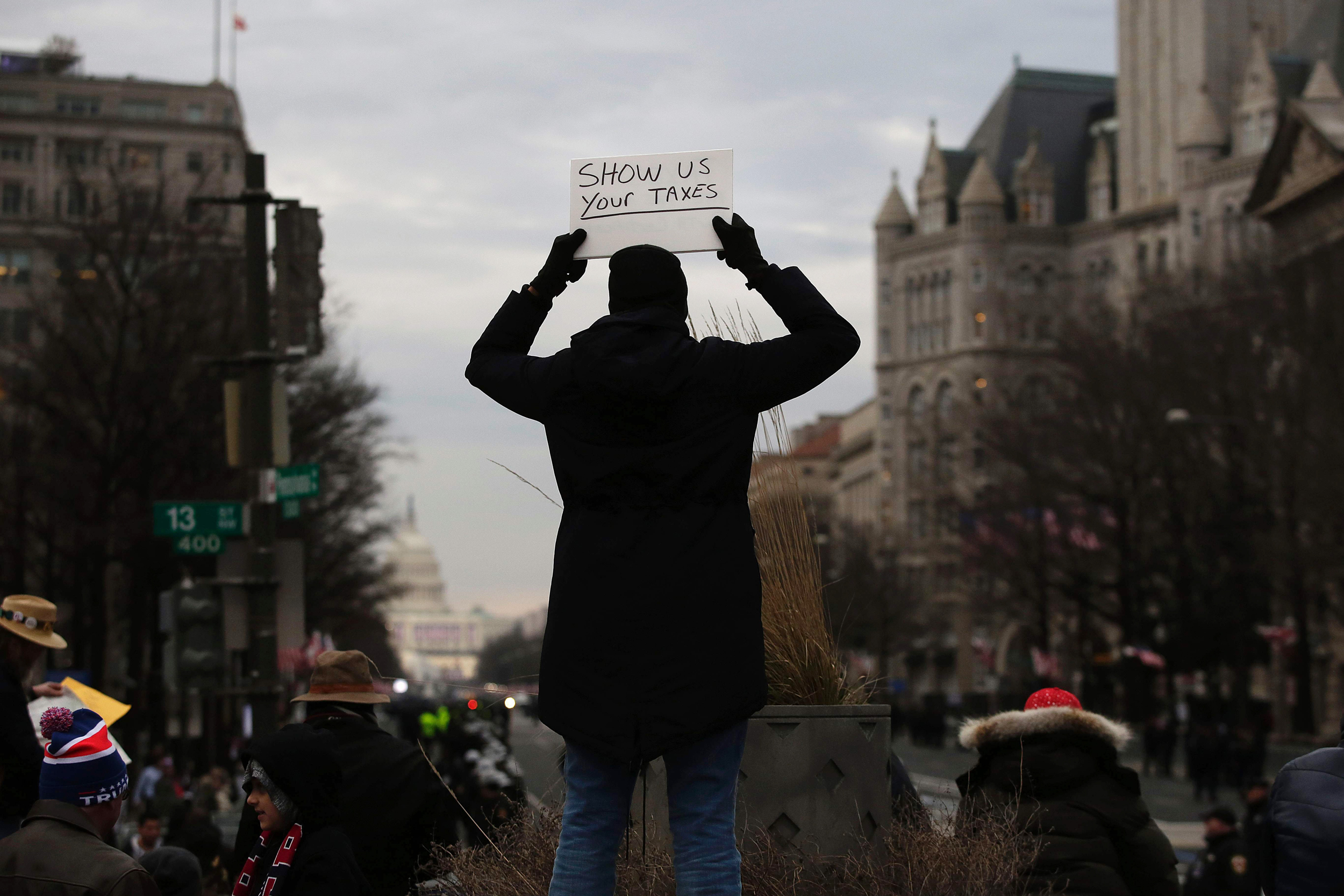 Image: A person holds up a sign in protest before the presidential inauguration of Donald Trump