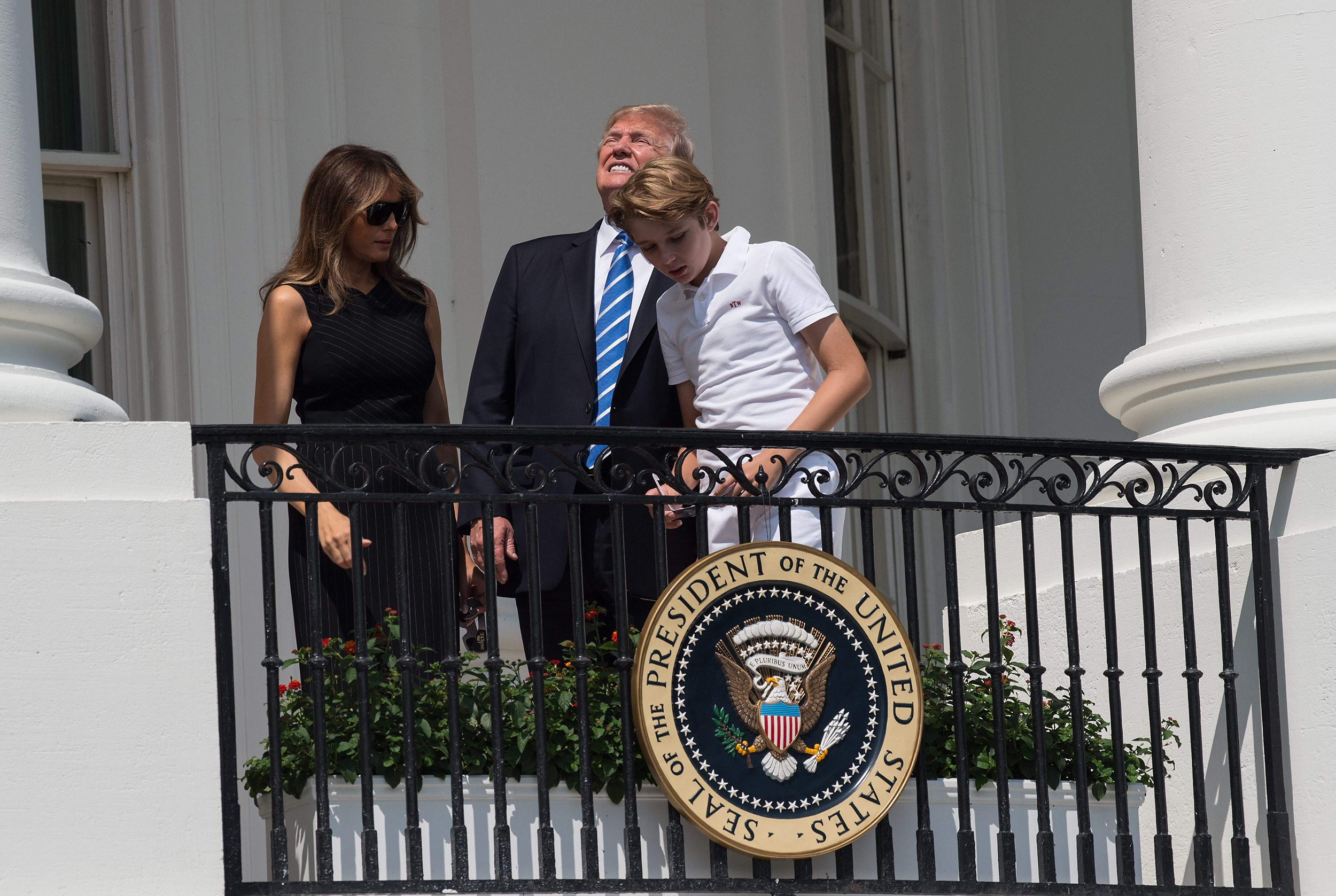 Image: President Donald Trump, First Lady Melania Trump and son Barron look up at the partial solar eclipse from the balcony of the White House in Washington, DC, on Aug. 21, 2017.