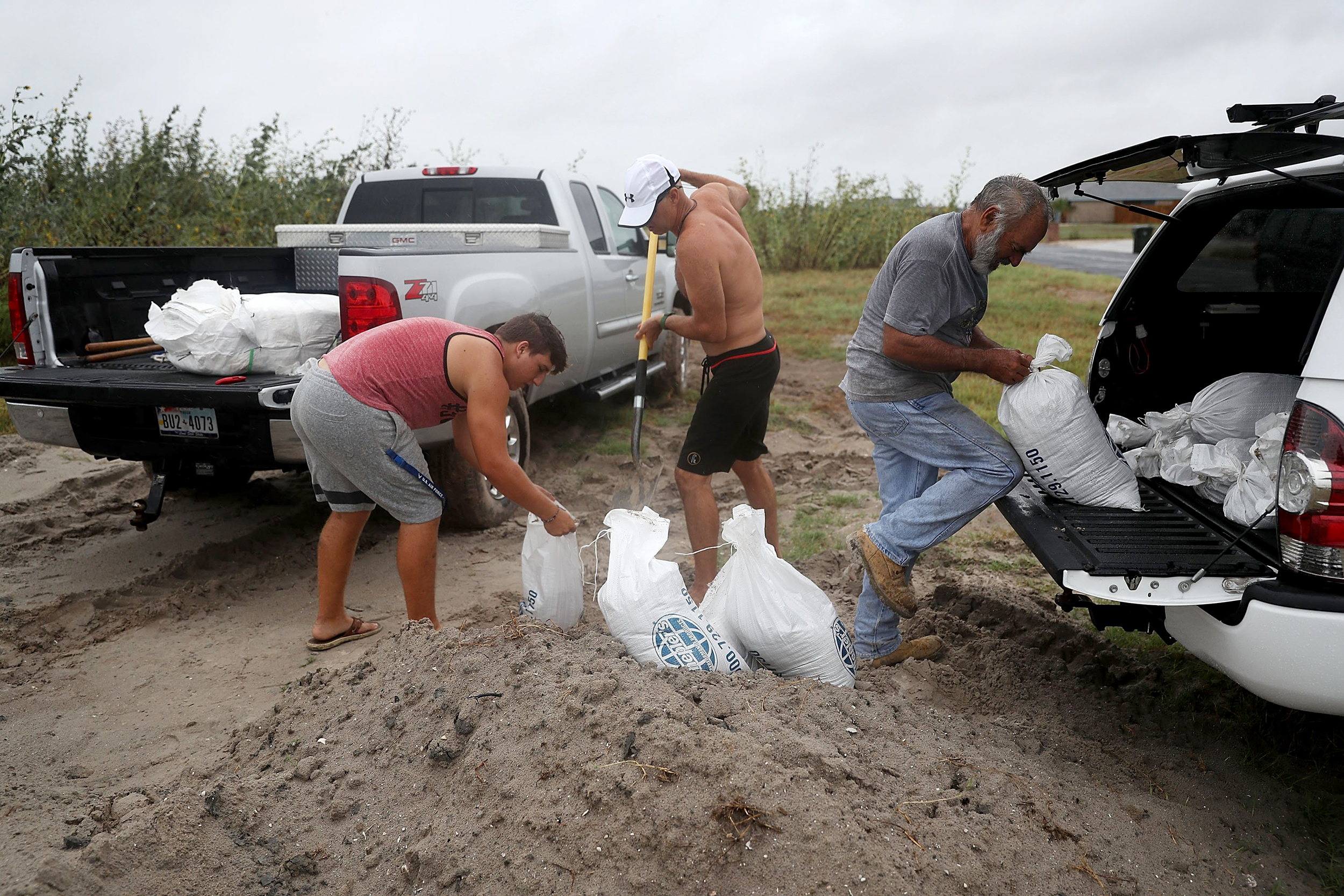 Image: Cody Munds, Lee Martin and John Pezzi, left to right, fill sandbags as people prepare for approaching Hurricane Harvey on Aug. 25, 2017 in Corpus Christi, Texas.