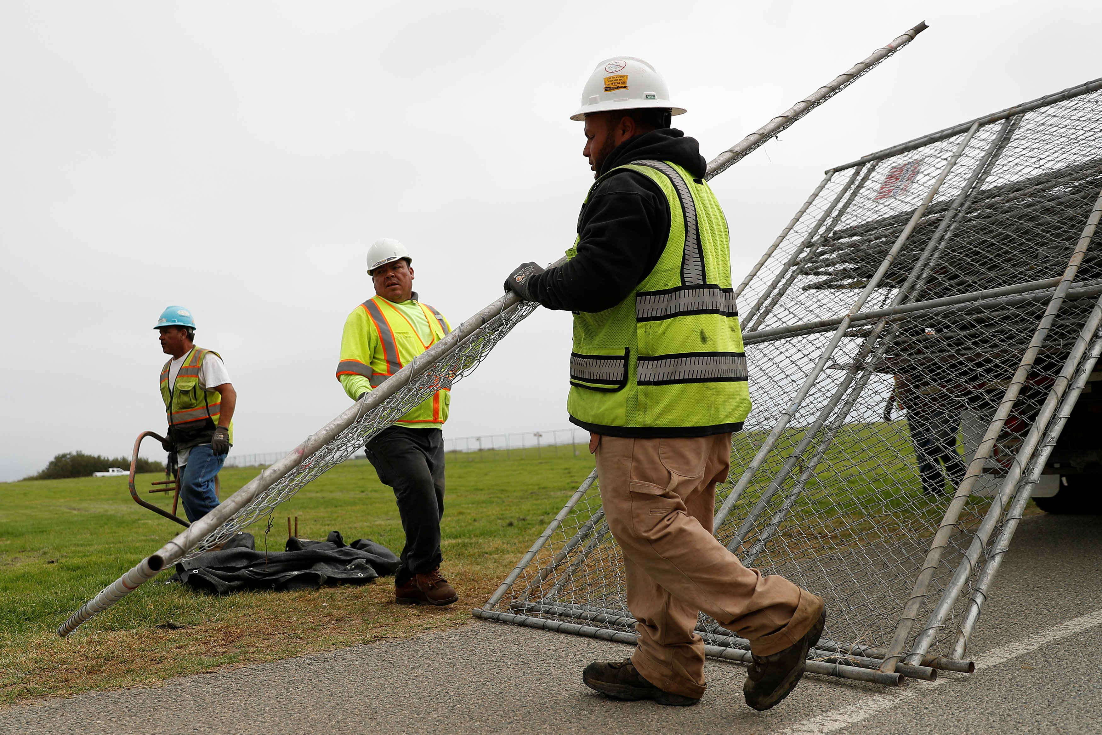 Image: Workers unload a chainlink fence at Crissy Field in anticipation of Saturday's Patriot Prayer rally and counter demonstration in San Francisco, California