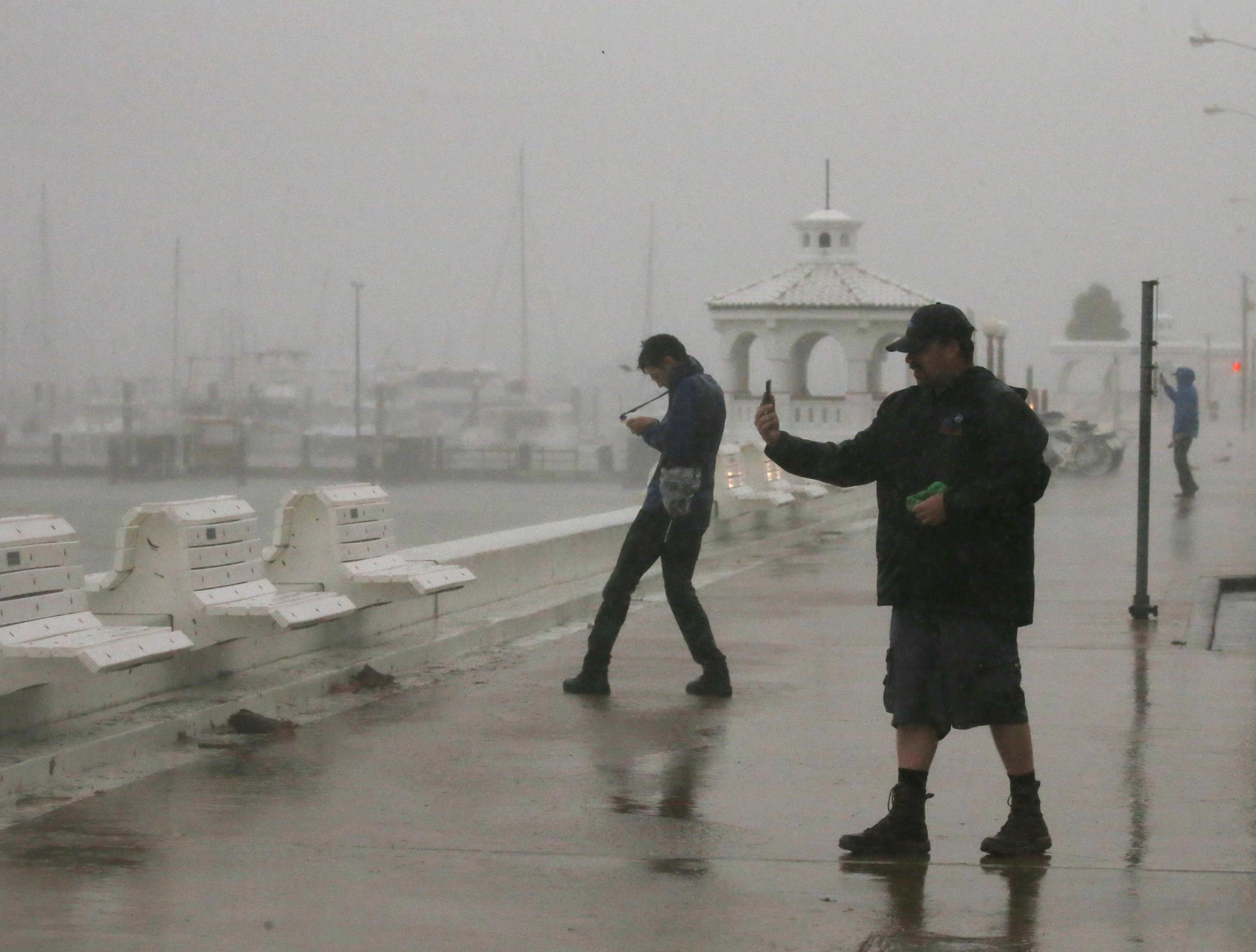 Image: A storm chaser films himself on a camera phone as Hurricane Harvey approaches, on the boardwalk in Corpus Christi