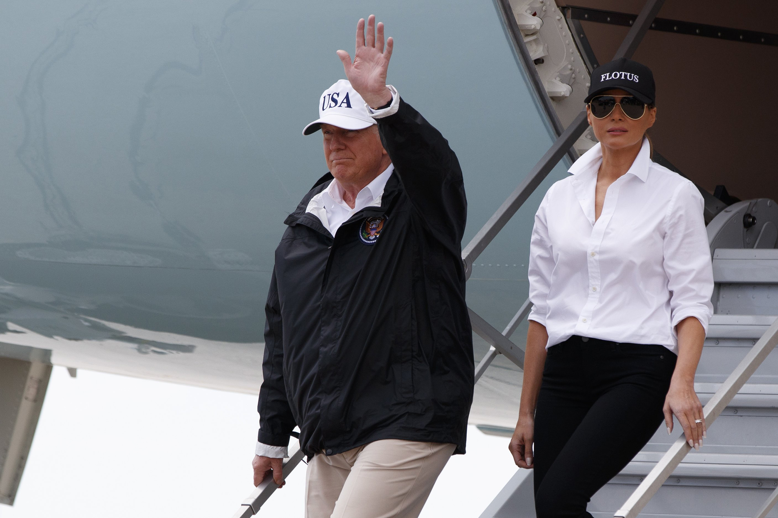 Image: President Donald Trump, accompanied by first lady Melania Trump, waves as they arrive on Air Force One at Corpus Christi International Airport