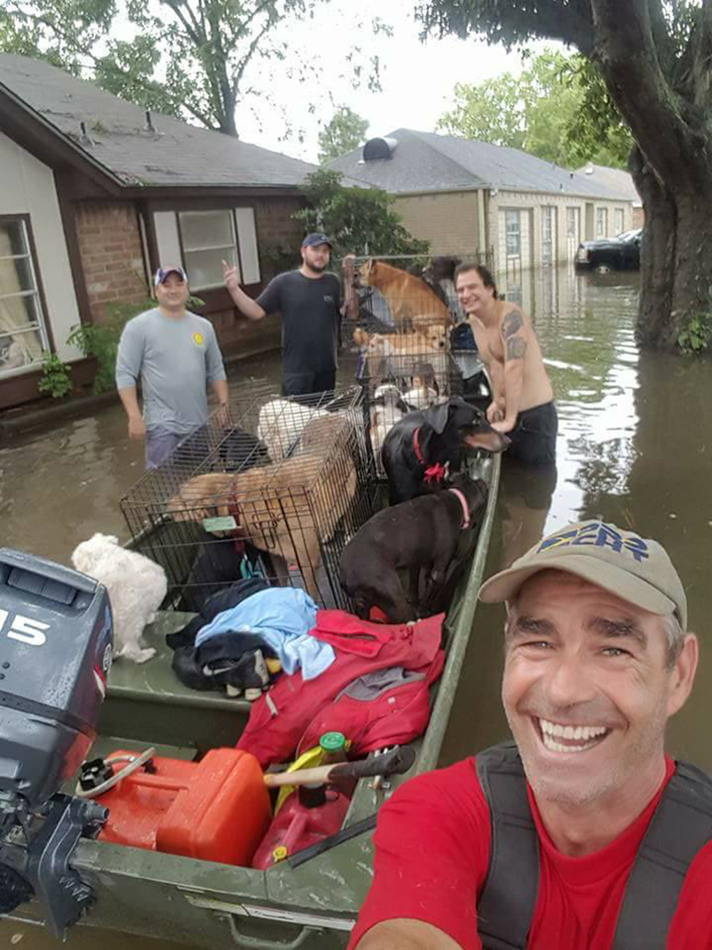 Image: Good Samaritans Buck Beasley, Jeremy Williams and Anthony Hernandez helped animal rescuer Betty Walter transport her dogs to safety in southeast Houston, Texas on August 30, 2017.