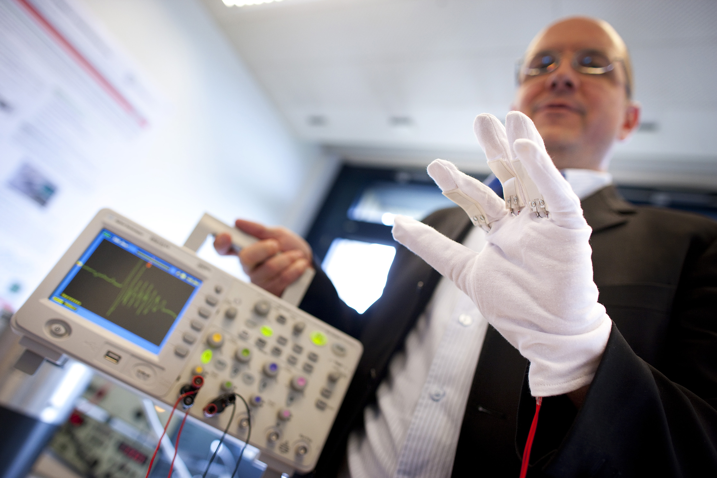 A scientist makes a demonstration of a piezoelectric energy harvesting glove during the media presentation of the Guardian Angels project at the Swiss Federal Institute of Technology in Ecublens