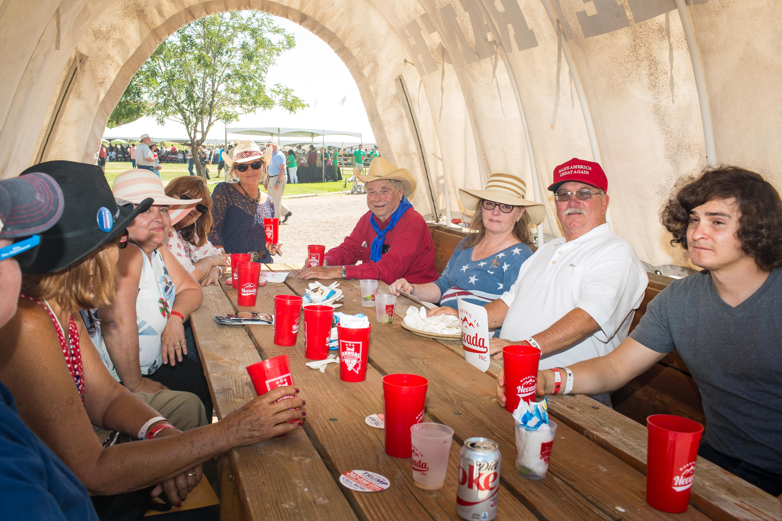 Image: John Mannelly, of Minden, Nevada, at right in white shirt, eats lunch under a covered wagon with friends and family