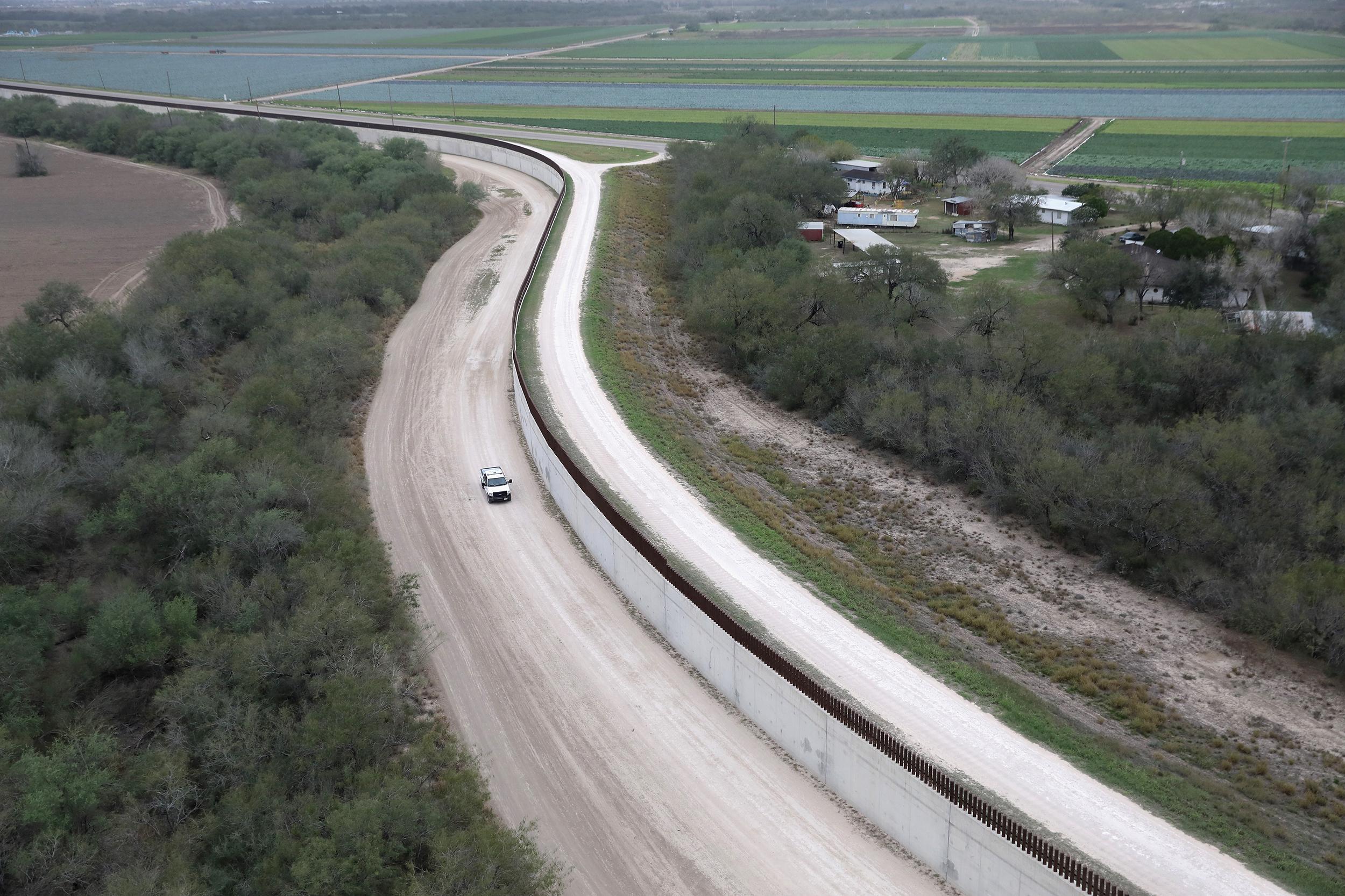 Image: A U.S. Border Patrol vehicle patrols next to a fence at the U.S.-Mexico border