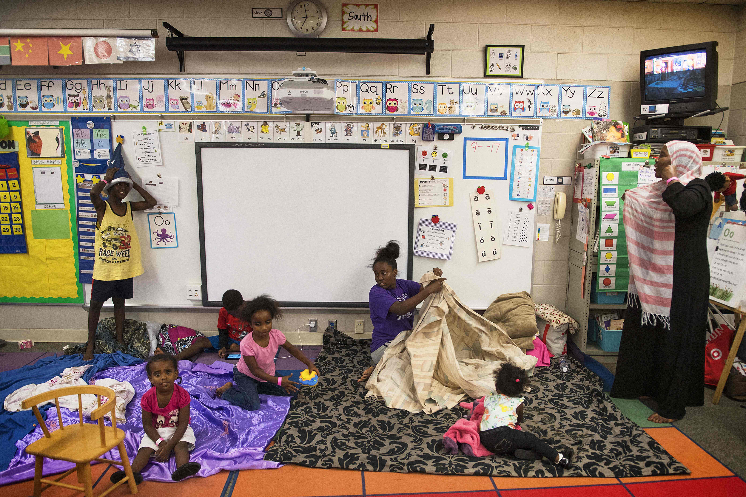 Image: A family makes sleeping arrangements in a classroom at a shelter within the Pizzo Elementary School in Tampa