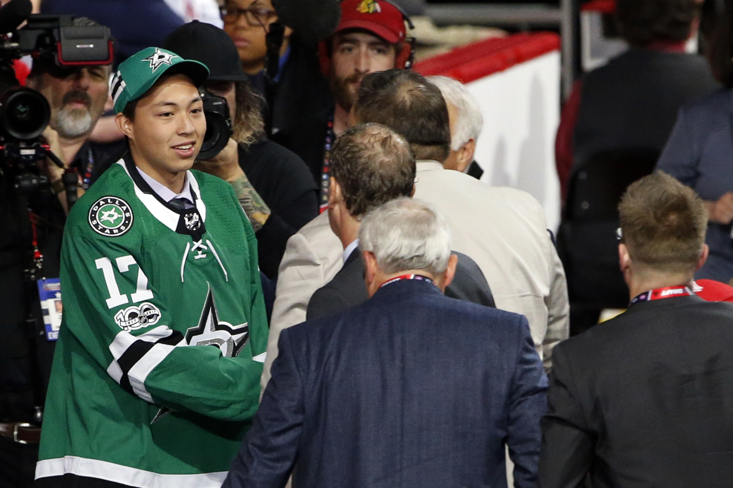 Image: Jason Robertson  talks with representatives from the Dallas Stars after being selected by the team during the second round of the 2017 NHL hockey draft