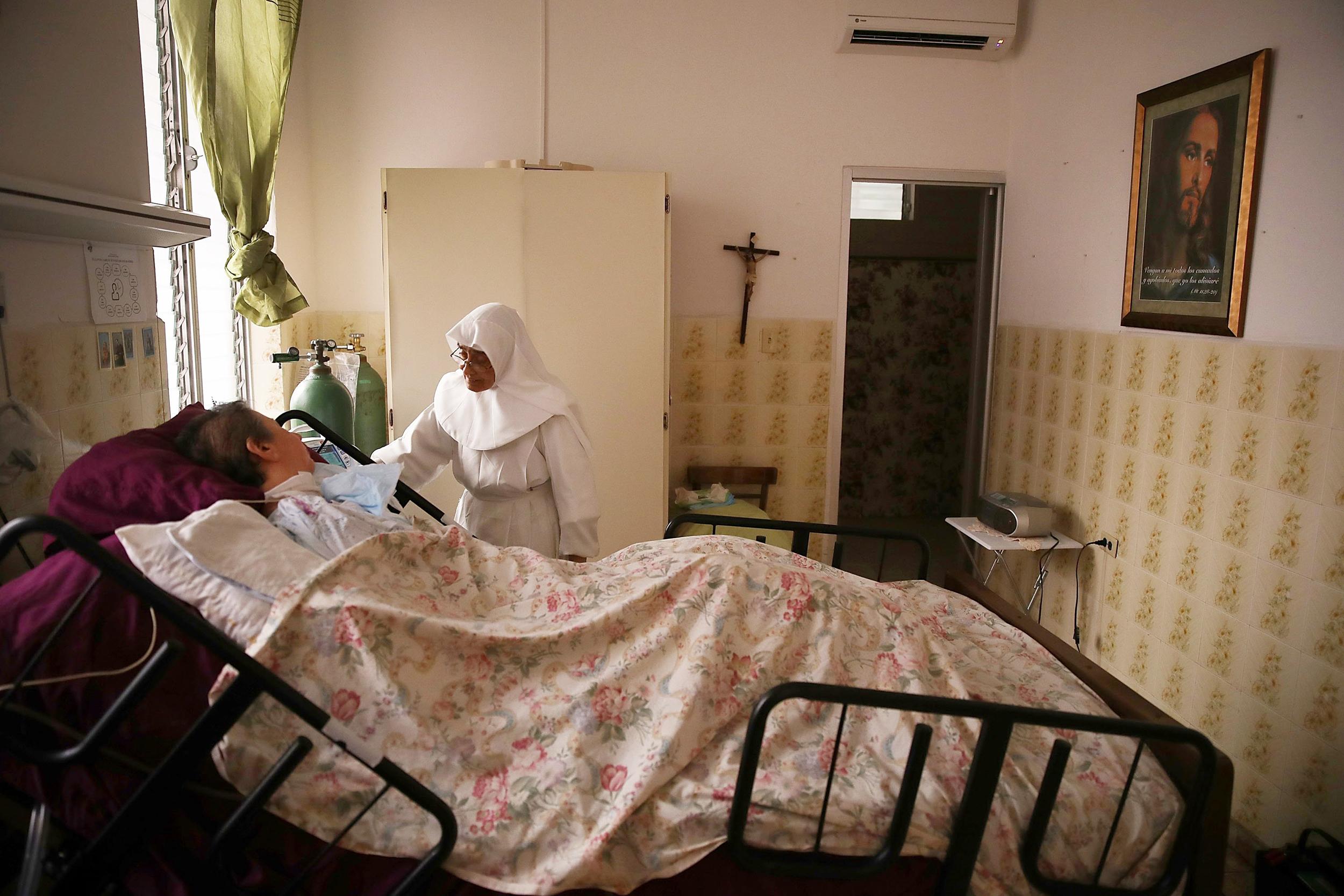 Image: Sister Gloria Flores checks in on a  patient at the Hermanitas de los Ancianos Desamparados facility which cares for the elderly