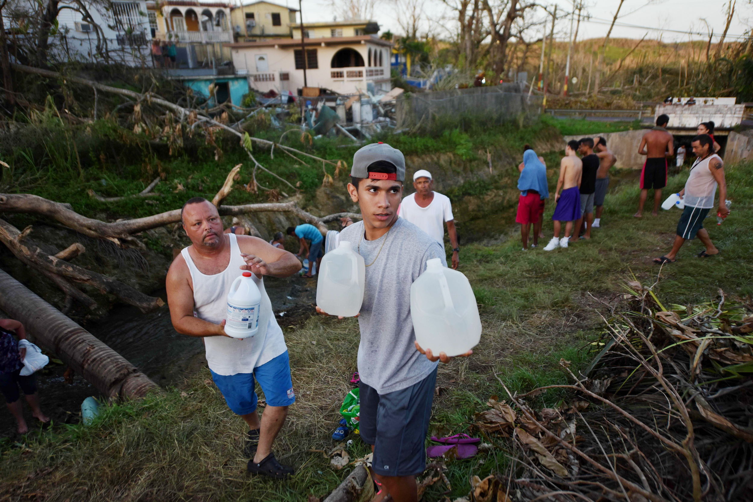 Image: People carry water in bottles retrieved from a canal due to lack of water following passage of Hurricane Maria, in Toa Alta, Puerto Rico