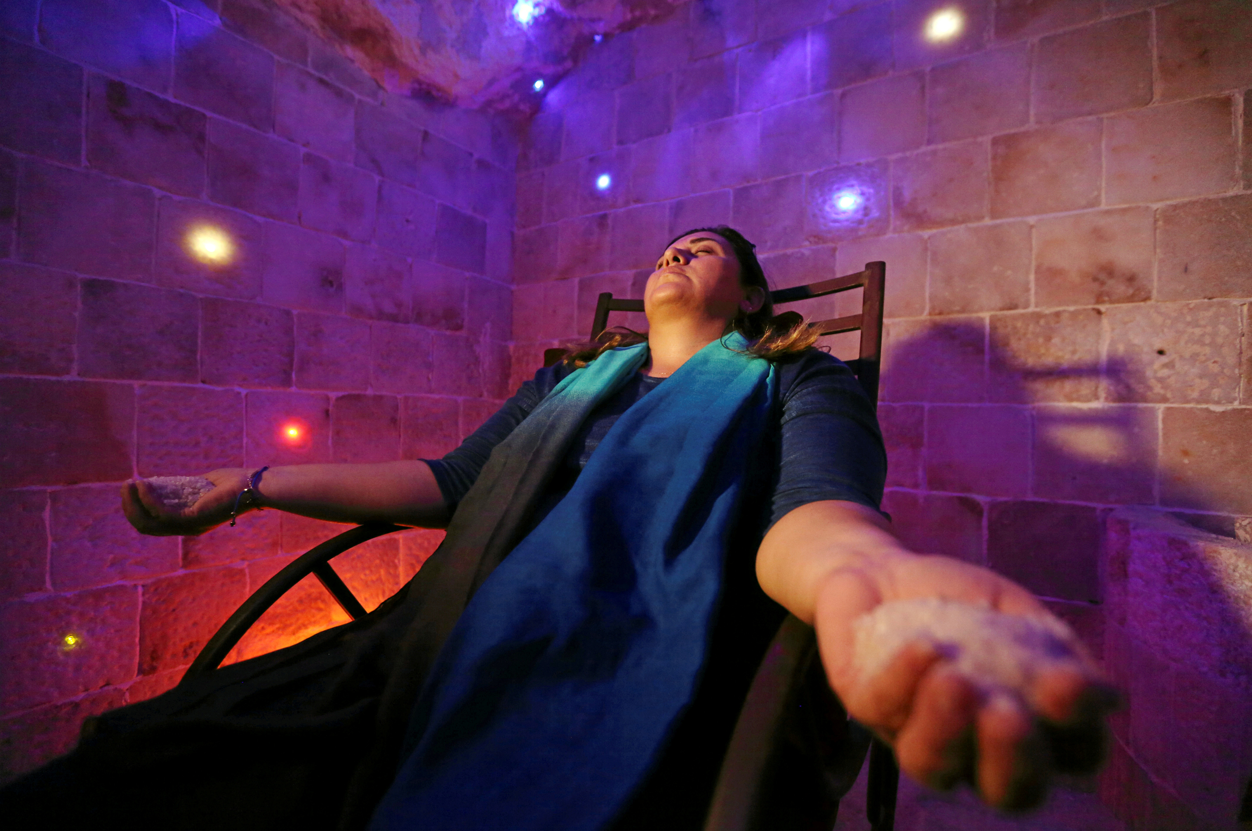 Image: A woman sits in a salt cave in Cairo