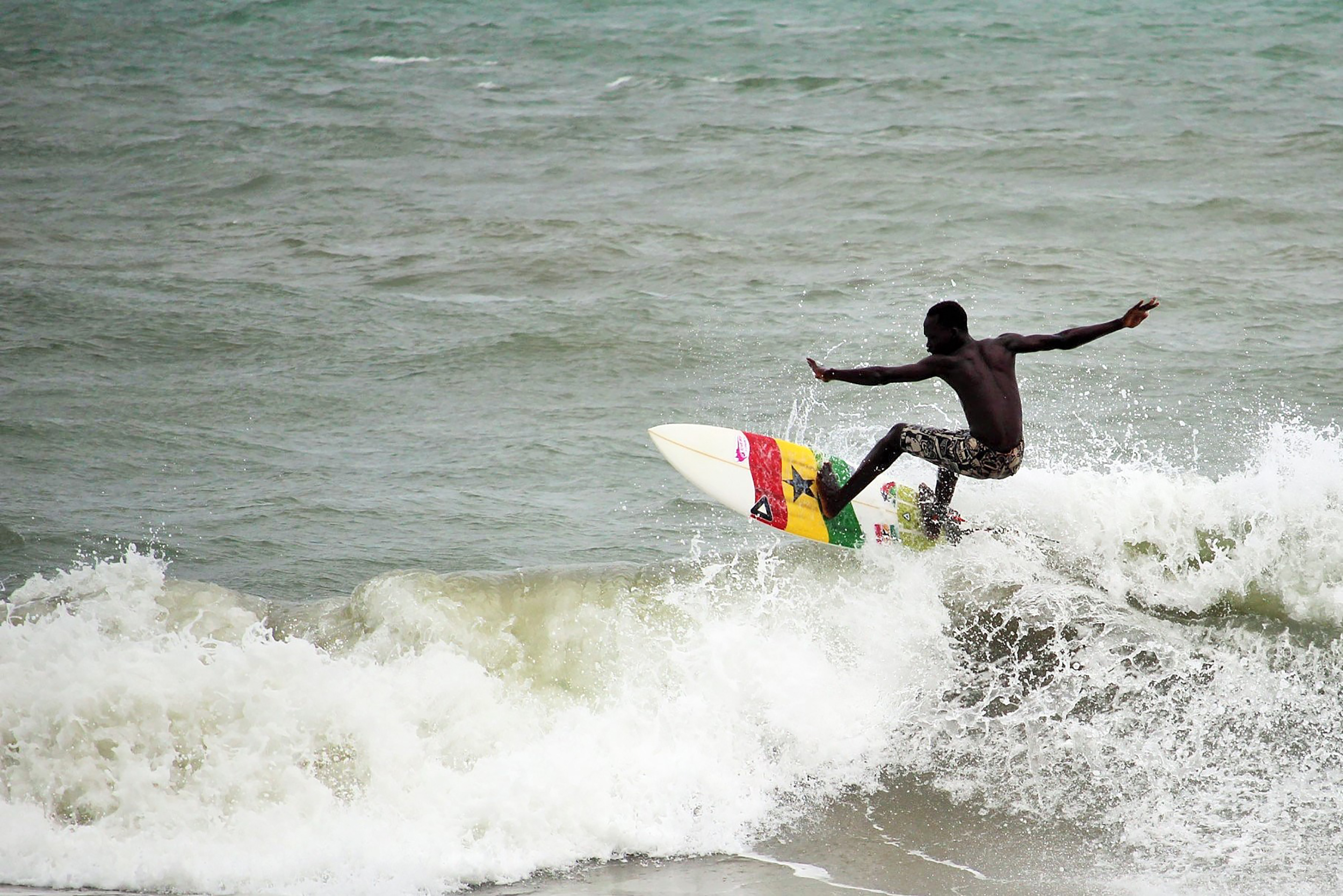 Image: A surfer surfs the ocean swell in Ghana