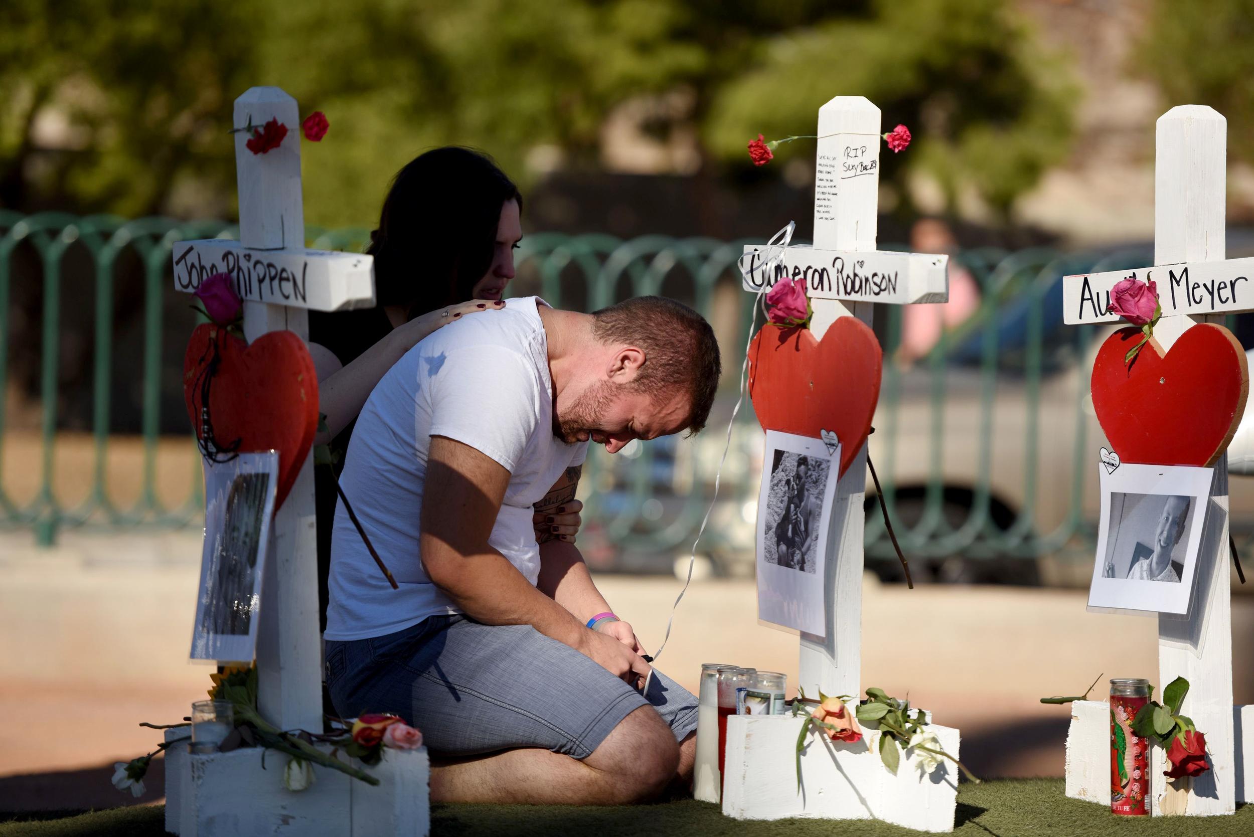 Image: Ethan Avanzino grieves beside a white cross