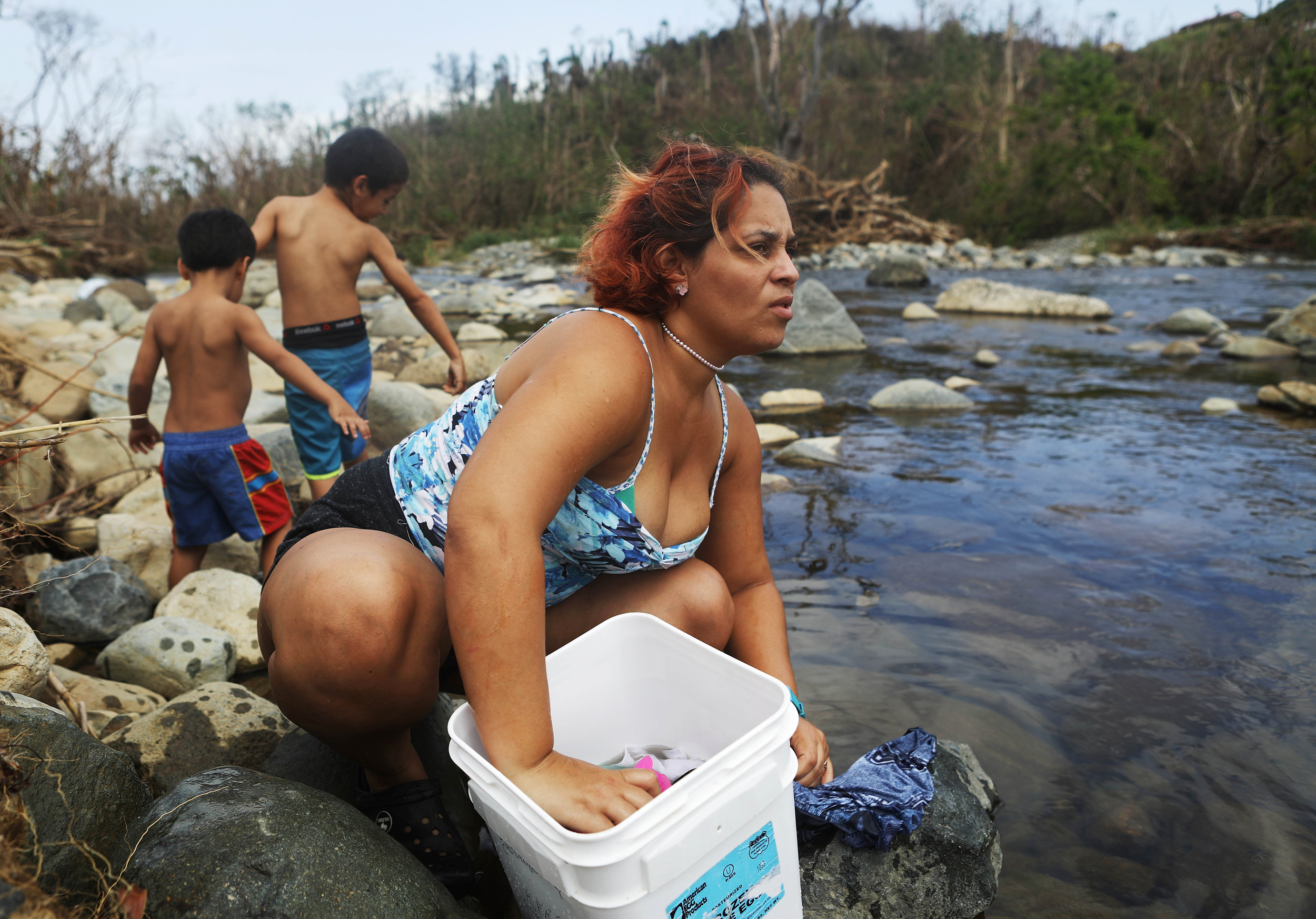 Image: A woman washes clothes with her sons in the Espiritu Santo river in Puerto Rico
