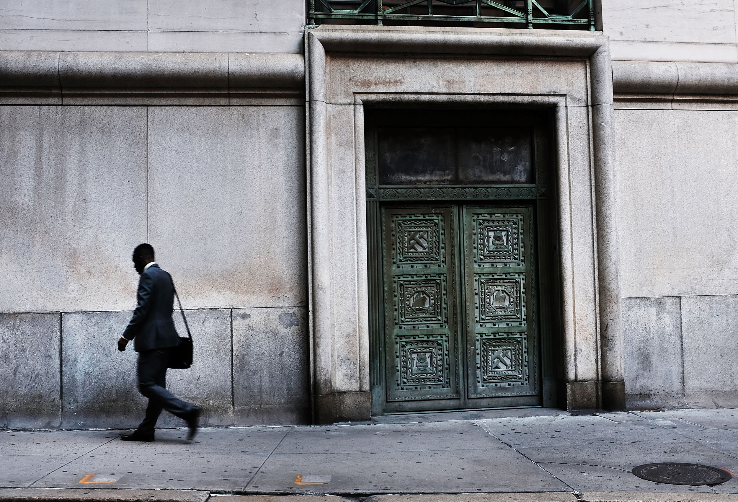 Image: A man walks through Manhattan's financial district