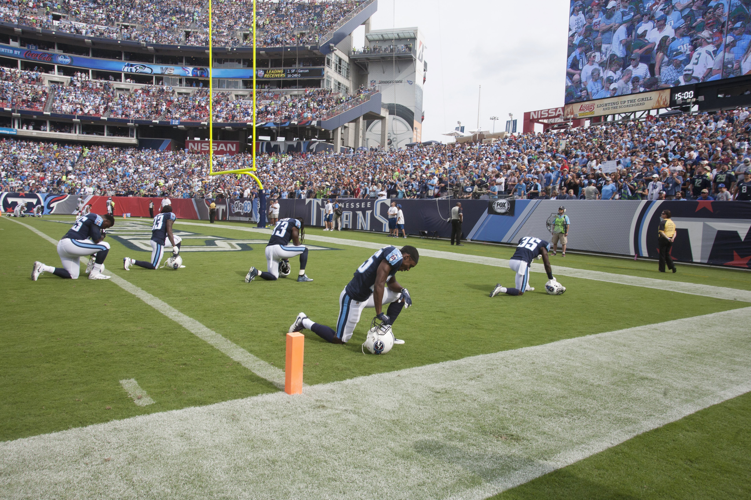 Image: Members of the Tennessee Titans kneel at the end zone