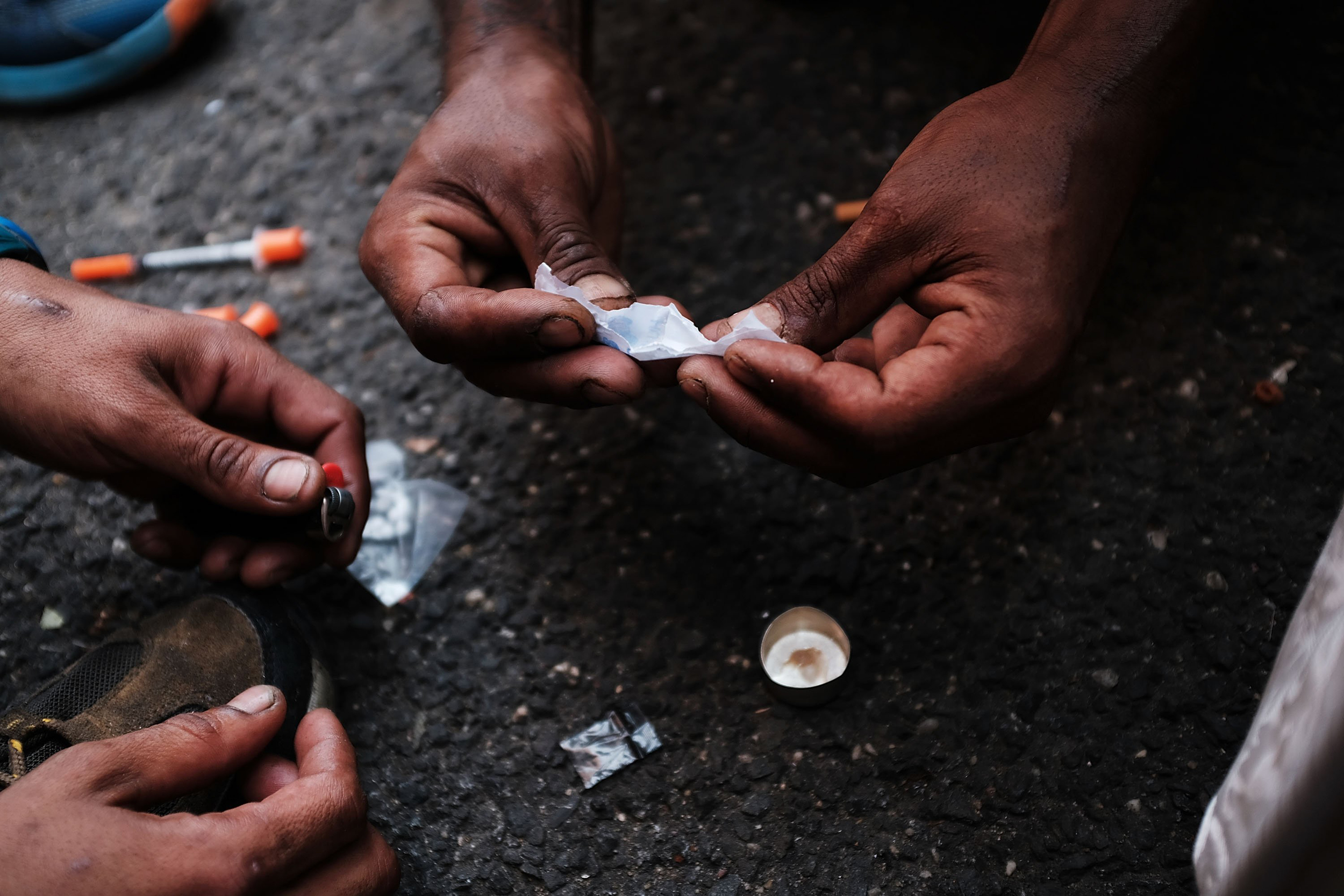 Image: Heroin users prepare to shoot up on the street in a South Bronx neighborhood