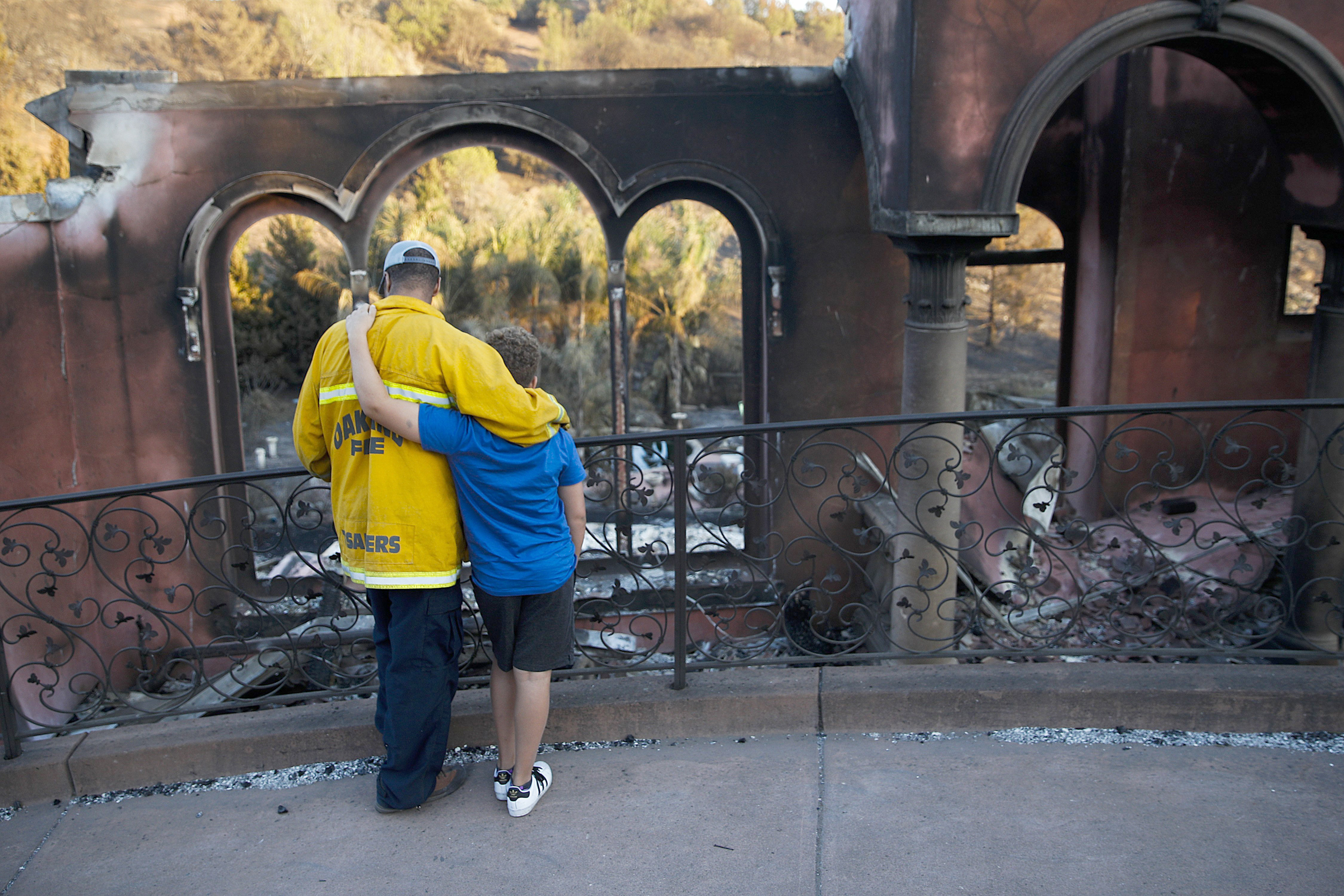 Image: Firefighter and son in front of neighbor's home