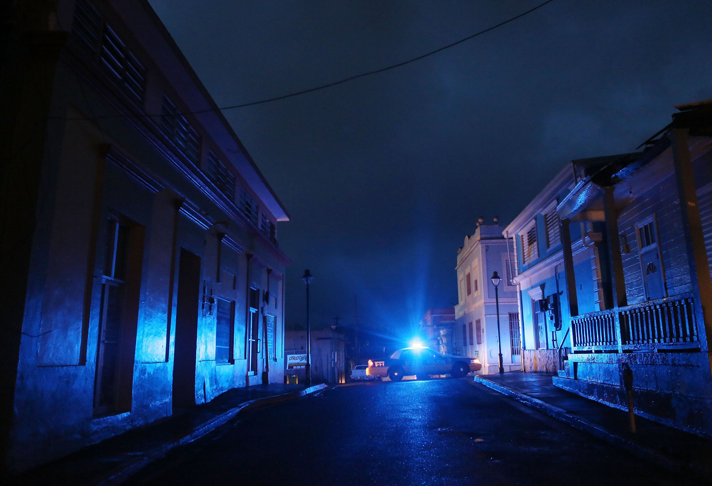 Image: A police car patrols on a darkened street