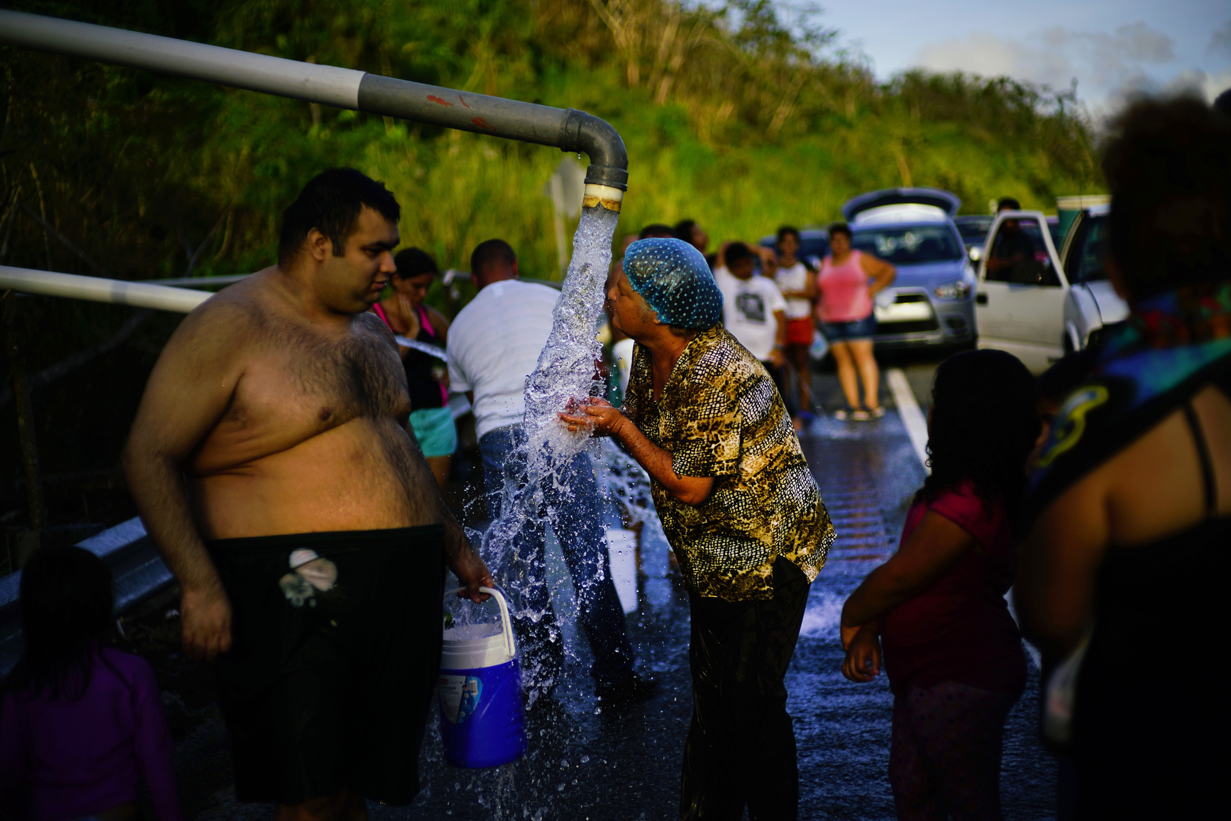Image: People bathe in water piped from a creek in the mountains