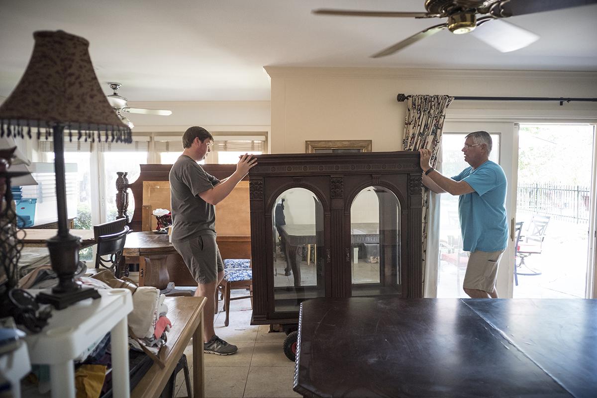Image: Rick Christie and his son Dalton move furniture