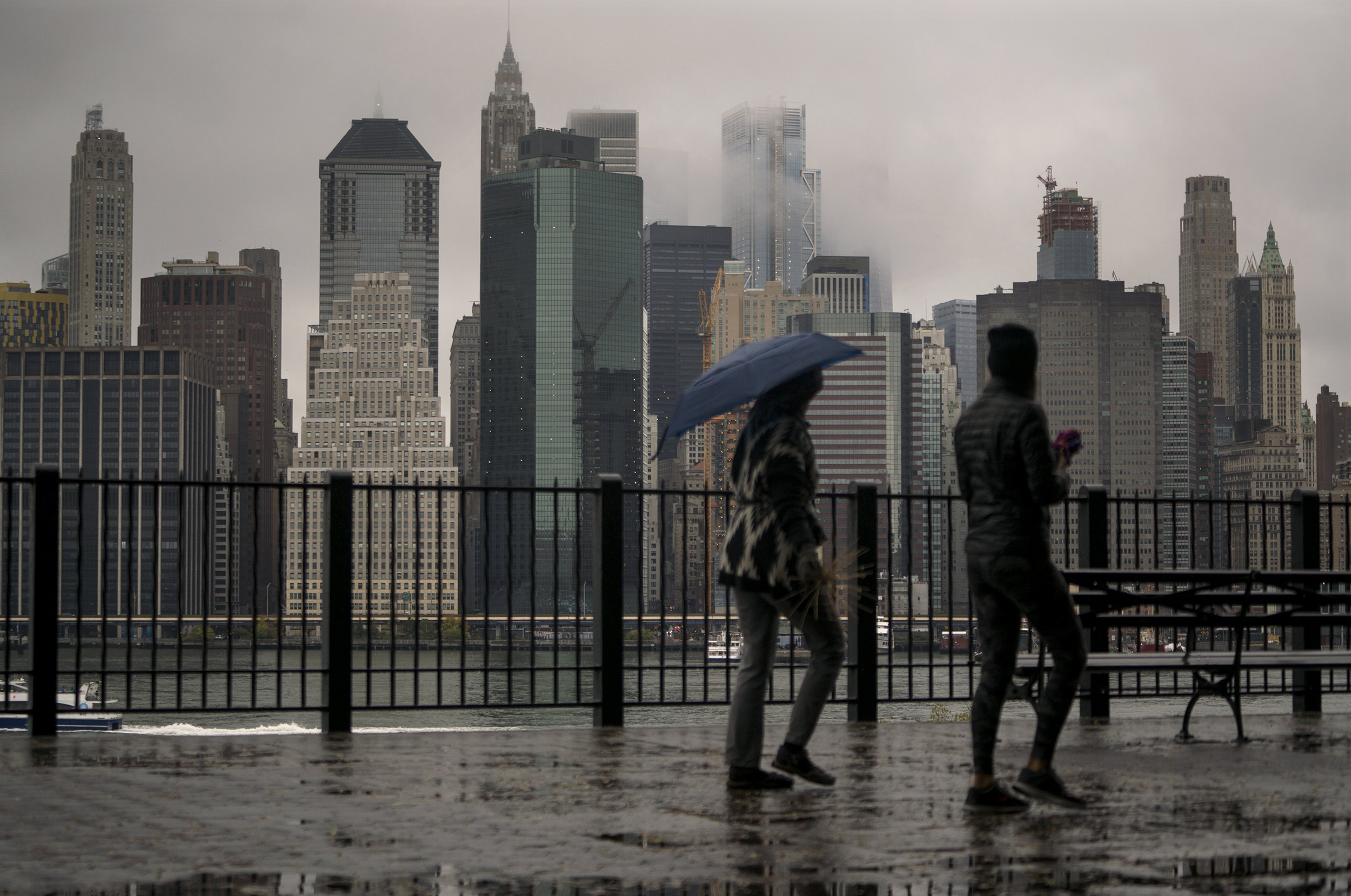 Image: Passersby walk along the Promenade in the Brooklyn Heights neighborhood as rain and clouds loom over lower Manhattan
