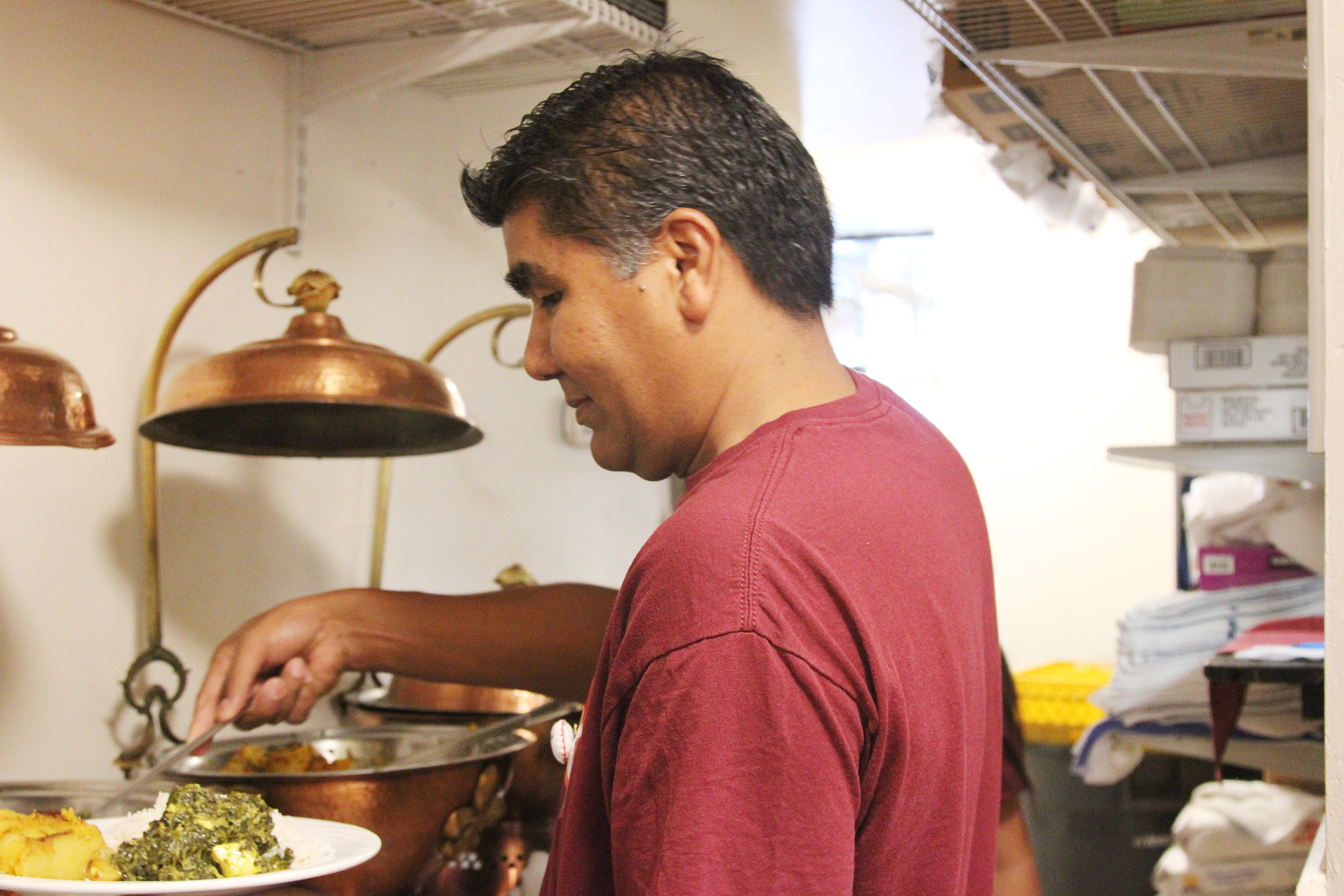 Karma Kitchen D.C. Coordinator Krishna Desar serves a meal for a guest during their October operation.