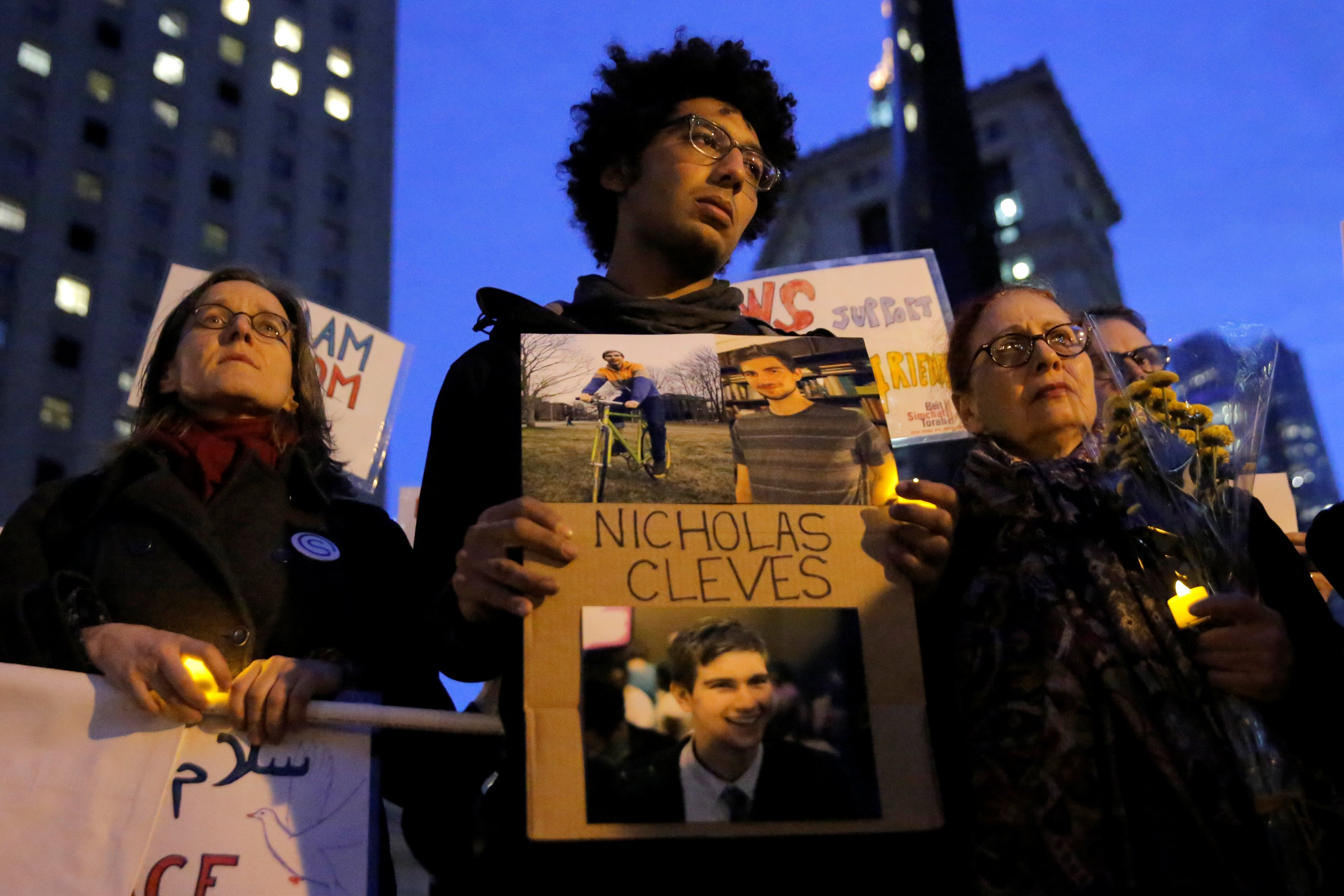 Image: Chancey stands with a sign featuring his friend and attack victim Cleves during a vigil in Foley Square in Manhattan