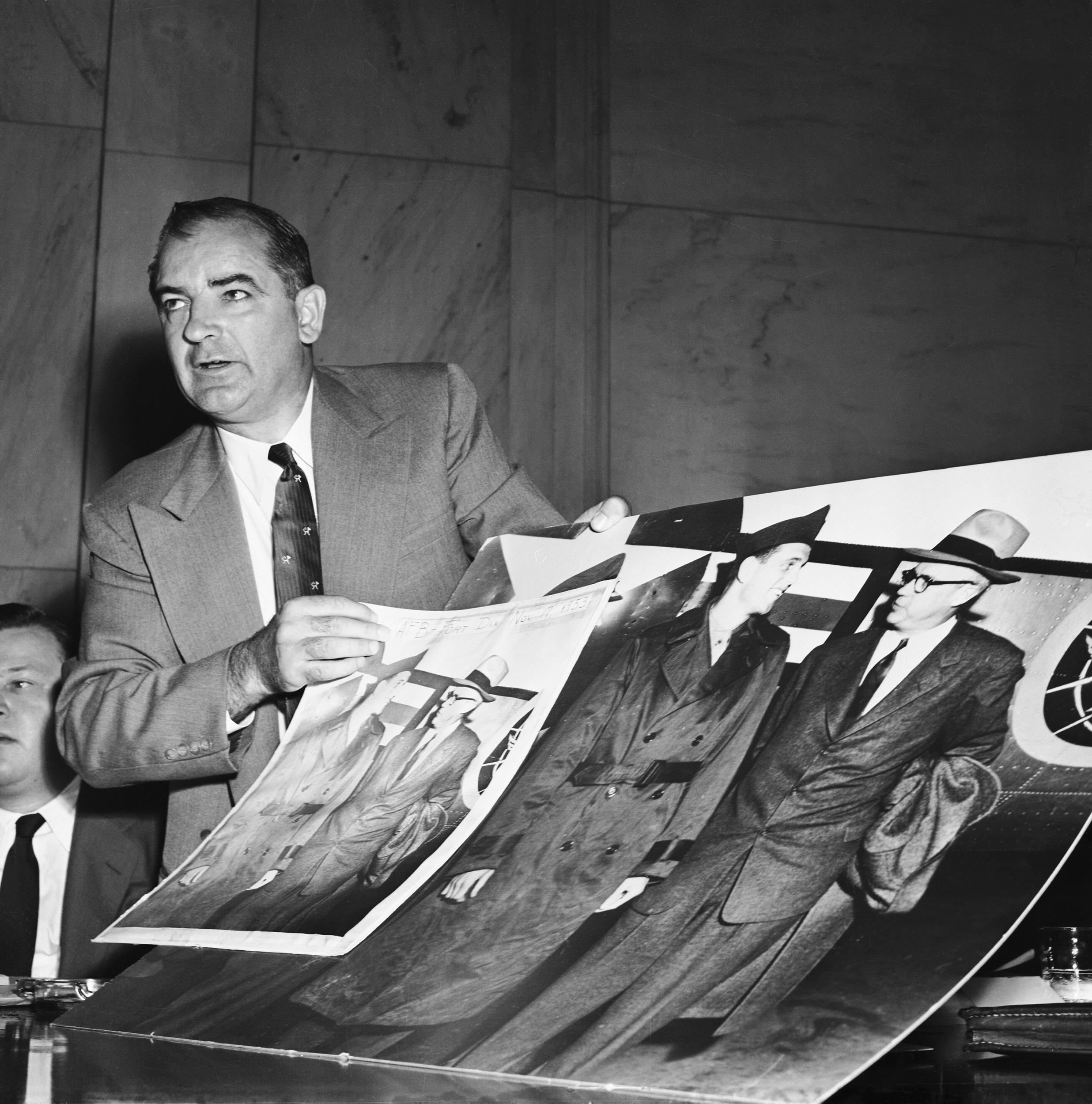 Image: Joseph McCarthy Holding Large Photographs