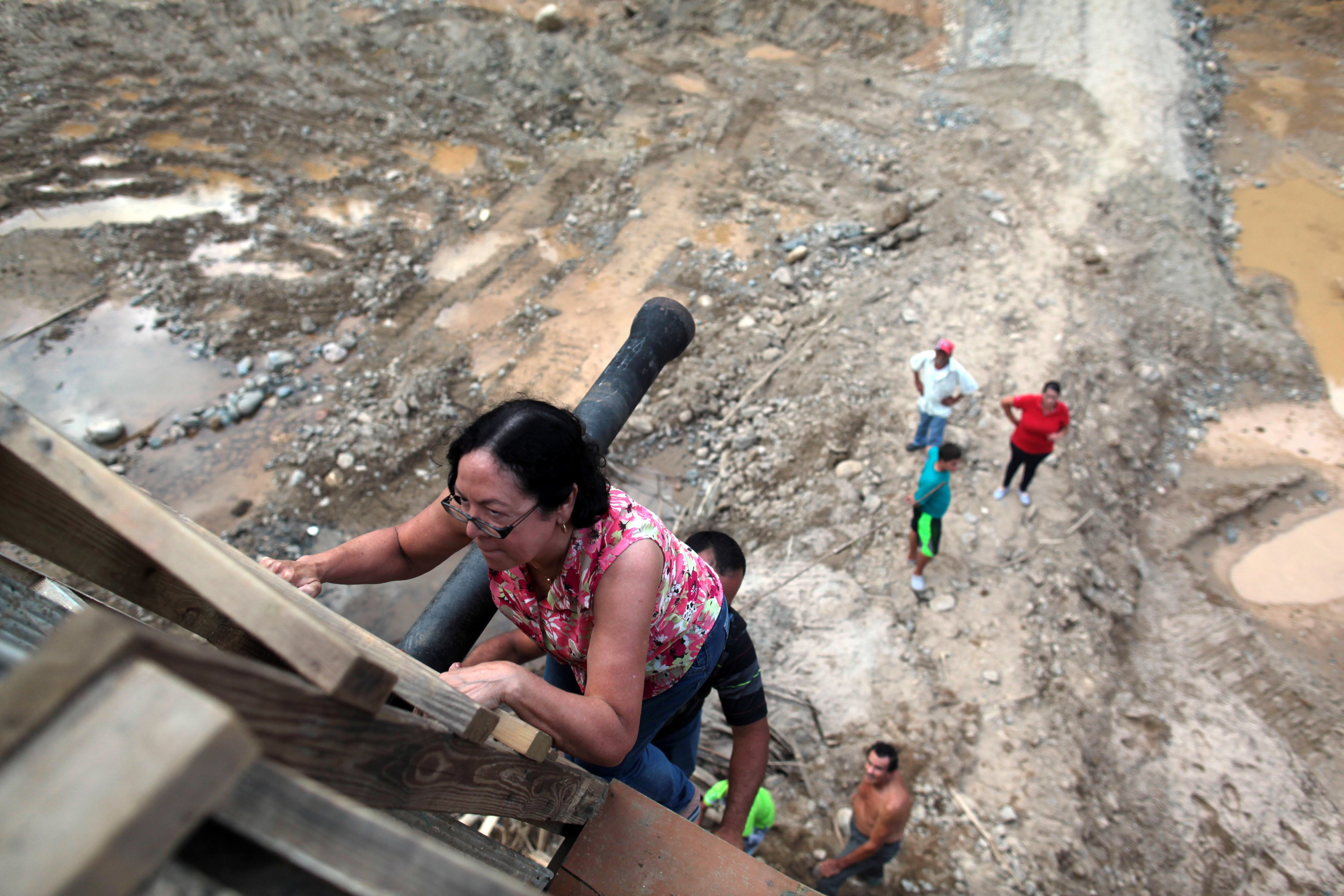 Image: People use a ladder to climb up a partially destroyed bridge after Hurricane Maria hit the area in September, in Utuado