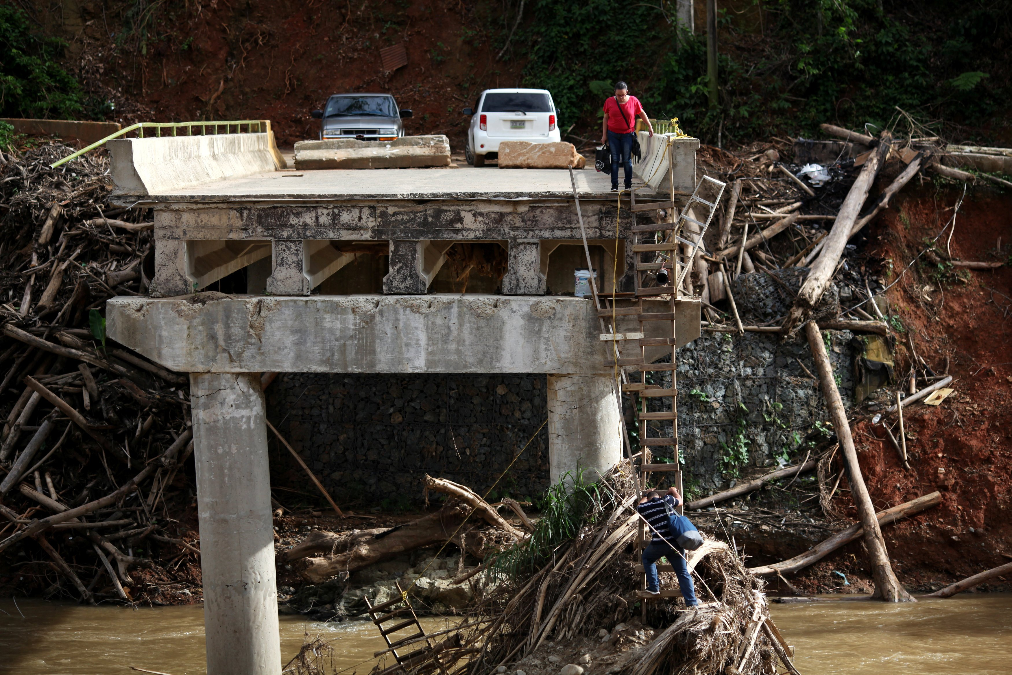 Image: A woman looks as her husband climbs down a ladder at a partially destroyed bridge, after Hurricane Maria hit the area in September, in Utuado