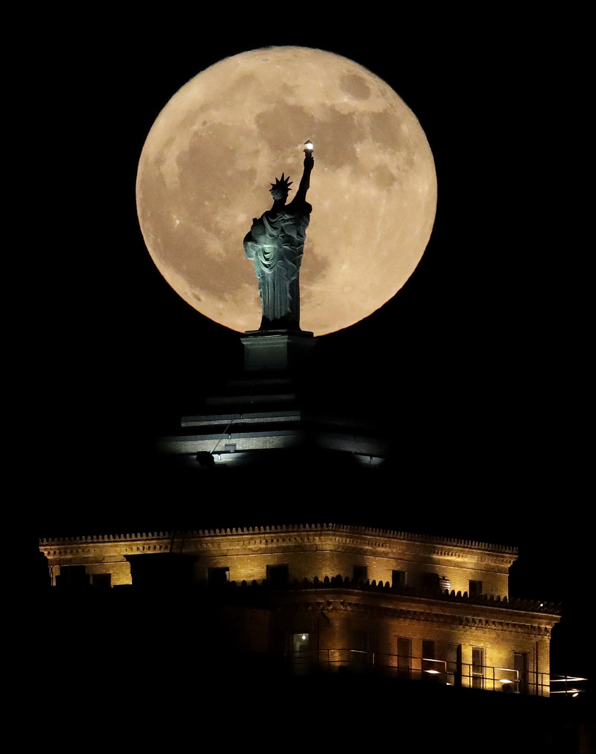 Image: A supermoon rises in front of a replica of the Statue of Liberty sitting atop the Liberty Building in downtown Buffalo