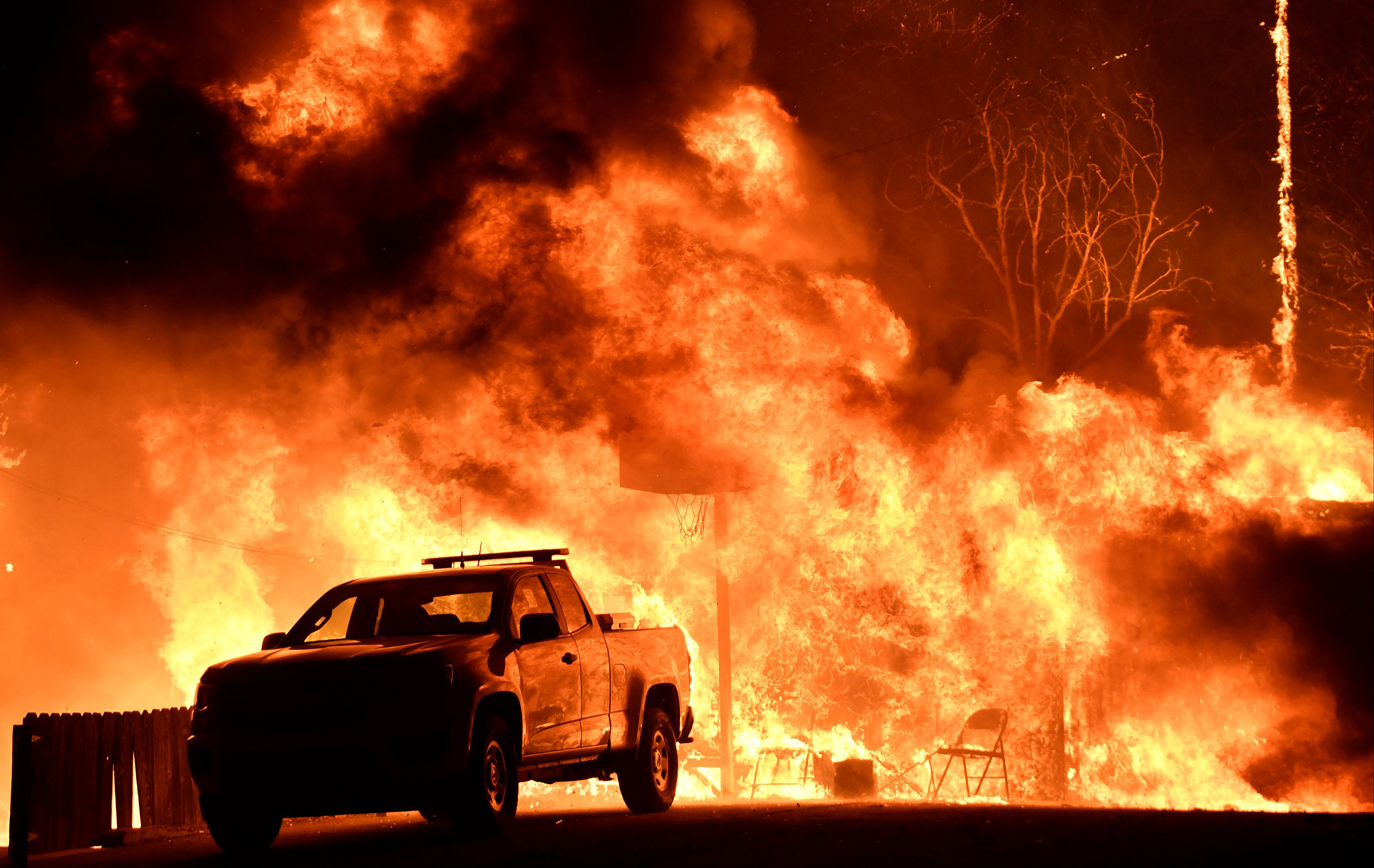 Image: Flames spread behind a vehicle from a Santa Ana wind-driven brush fire called the Thomas Fire in Santa Paula, California