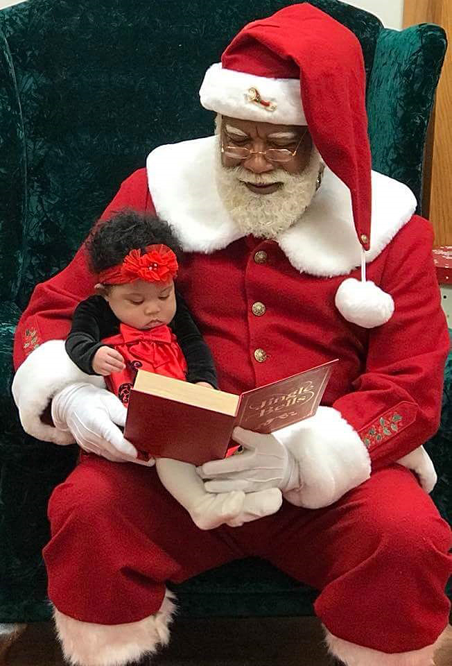 Image: Larry Jefferson sits with a child during a mall Santa Claus photo shoot.