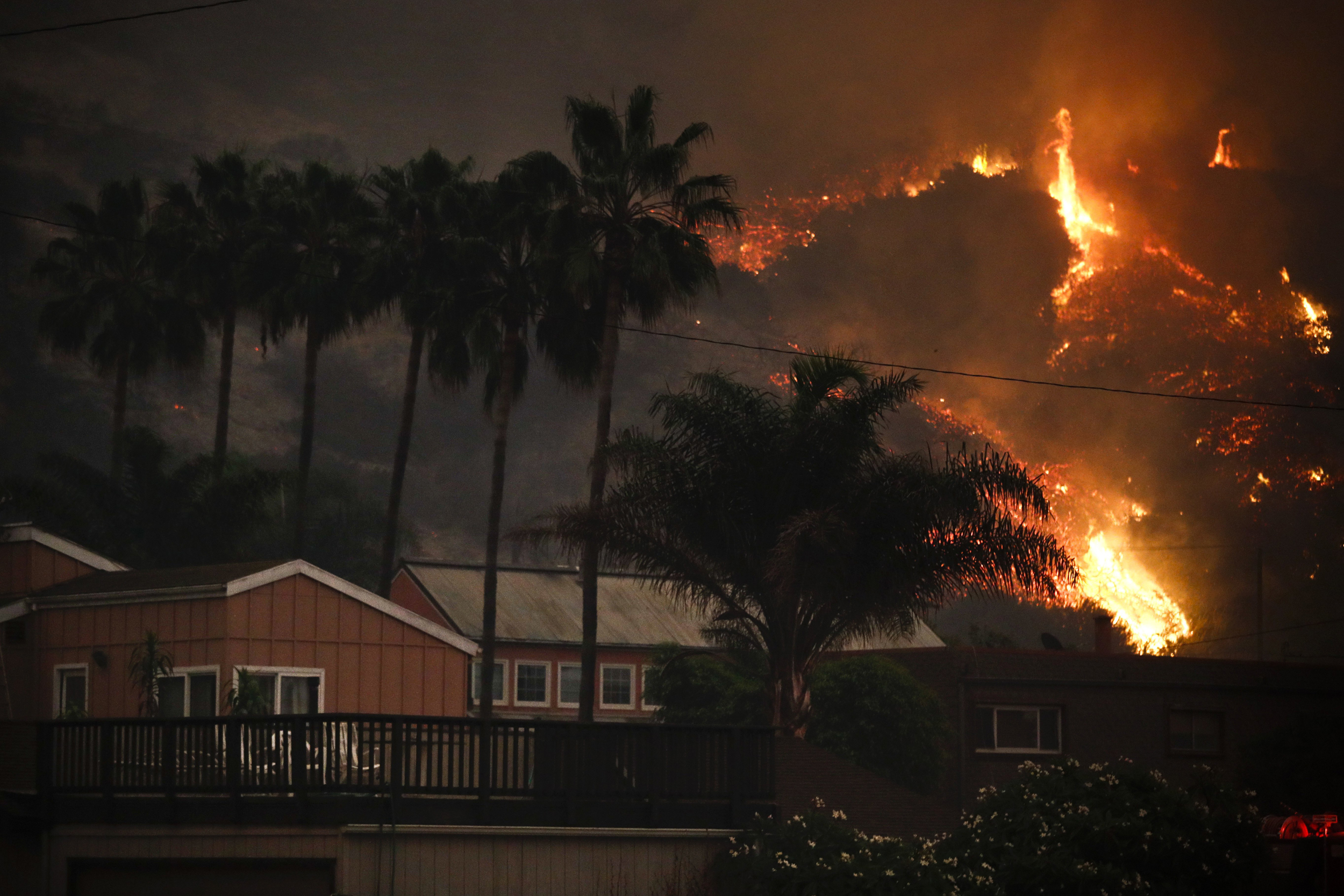Image: A wildfire threatens homes as it burns along a hillside in La Conchita