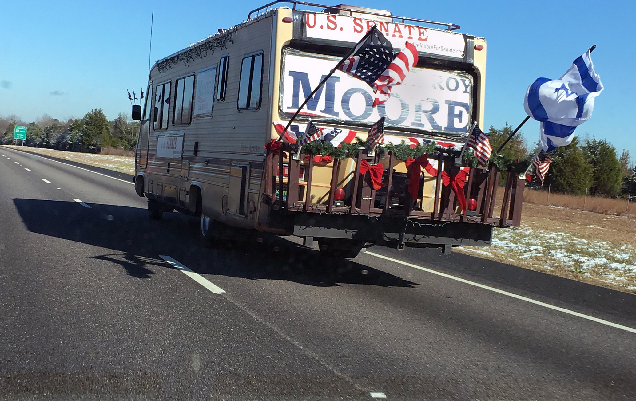 Image:A recreational vehicle decked with a 'Roy Moore for Senate' sign and the American and Israeli flags drives north on I-65 toward Montgomery, Alabama, on Dec. 9, 2017.