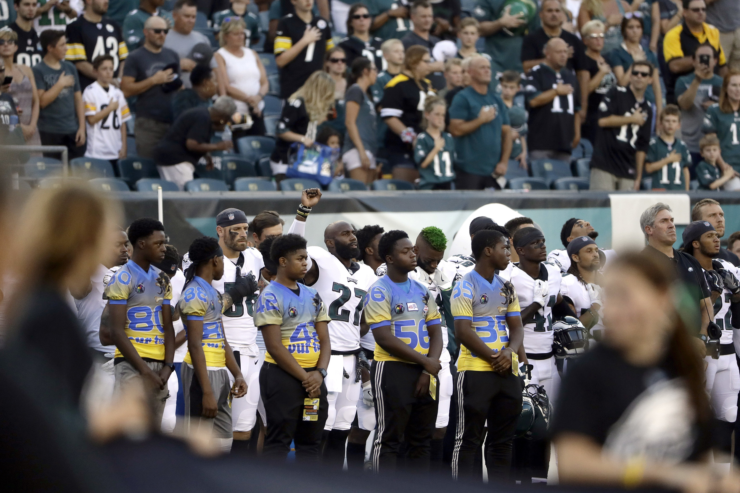 Some NFL players kneel or raise fists during anthem before