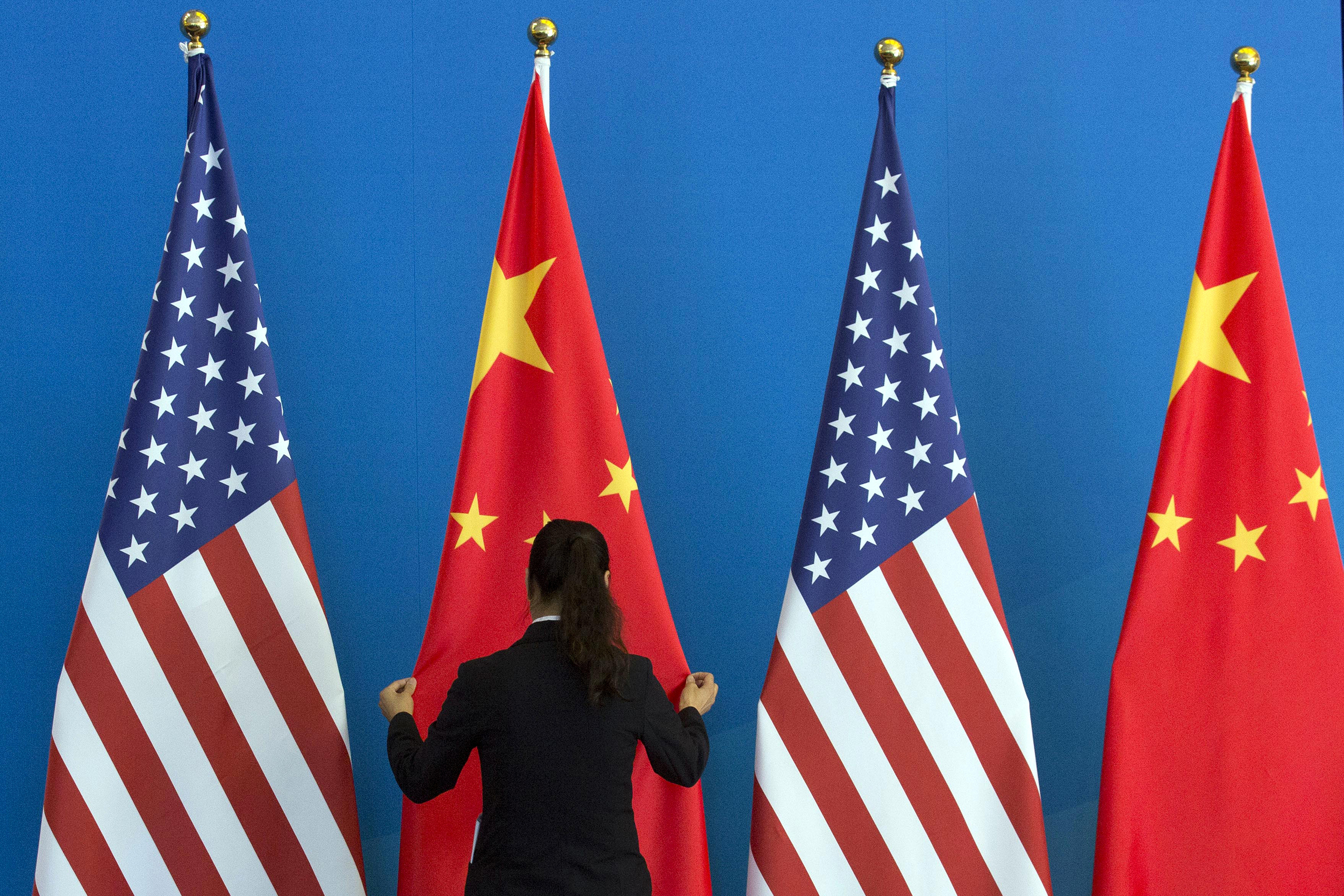 Image: A woman adjusts the Chinese national flag near U.S. national flags