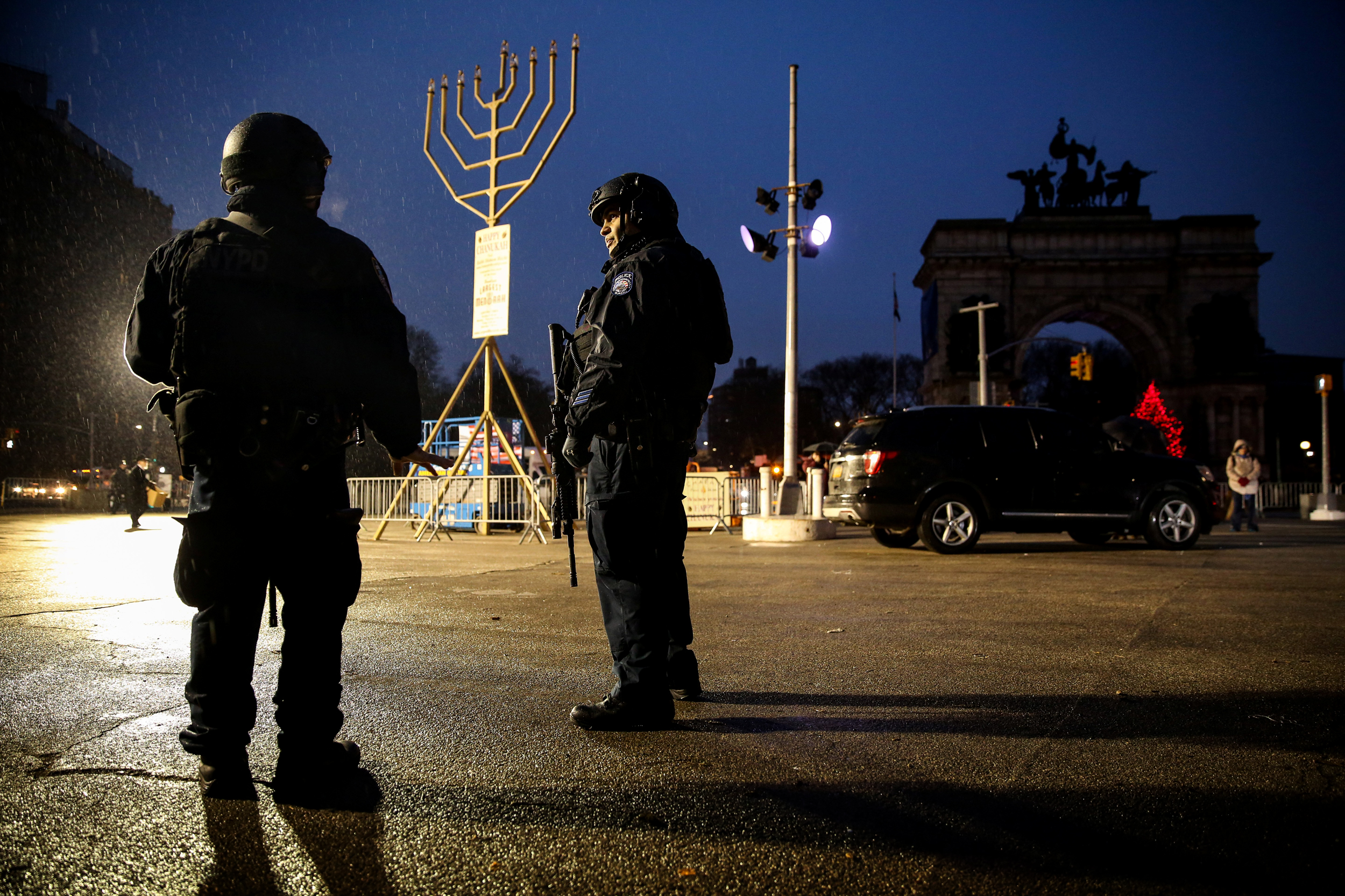 Image: New York Police officers stand guard ahead of a gathering at Brooklyn's Grand Army Plaza for the victims of a machete attack at a Hannukah celebration the day before in Monsey, N.Y., on Dec. 29, 2019.